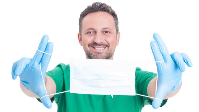 Doctor holding surgical or surgeon mask with text area or copy space on it