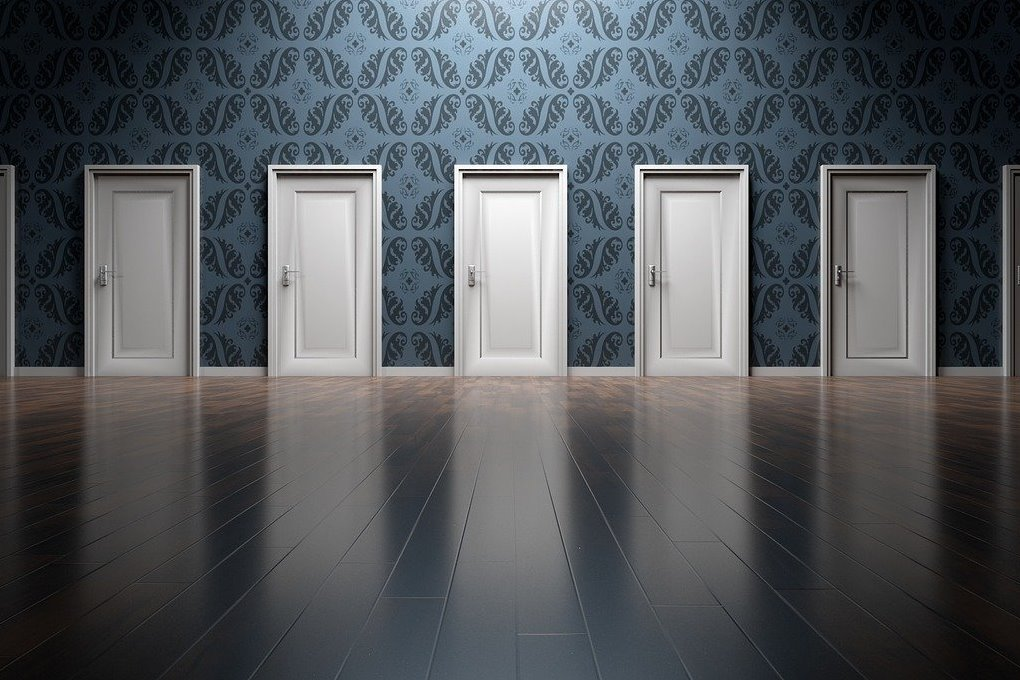 5 white doors on a wall with blue pattern wall paper