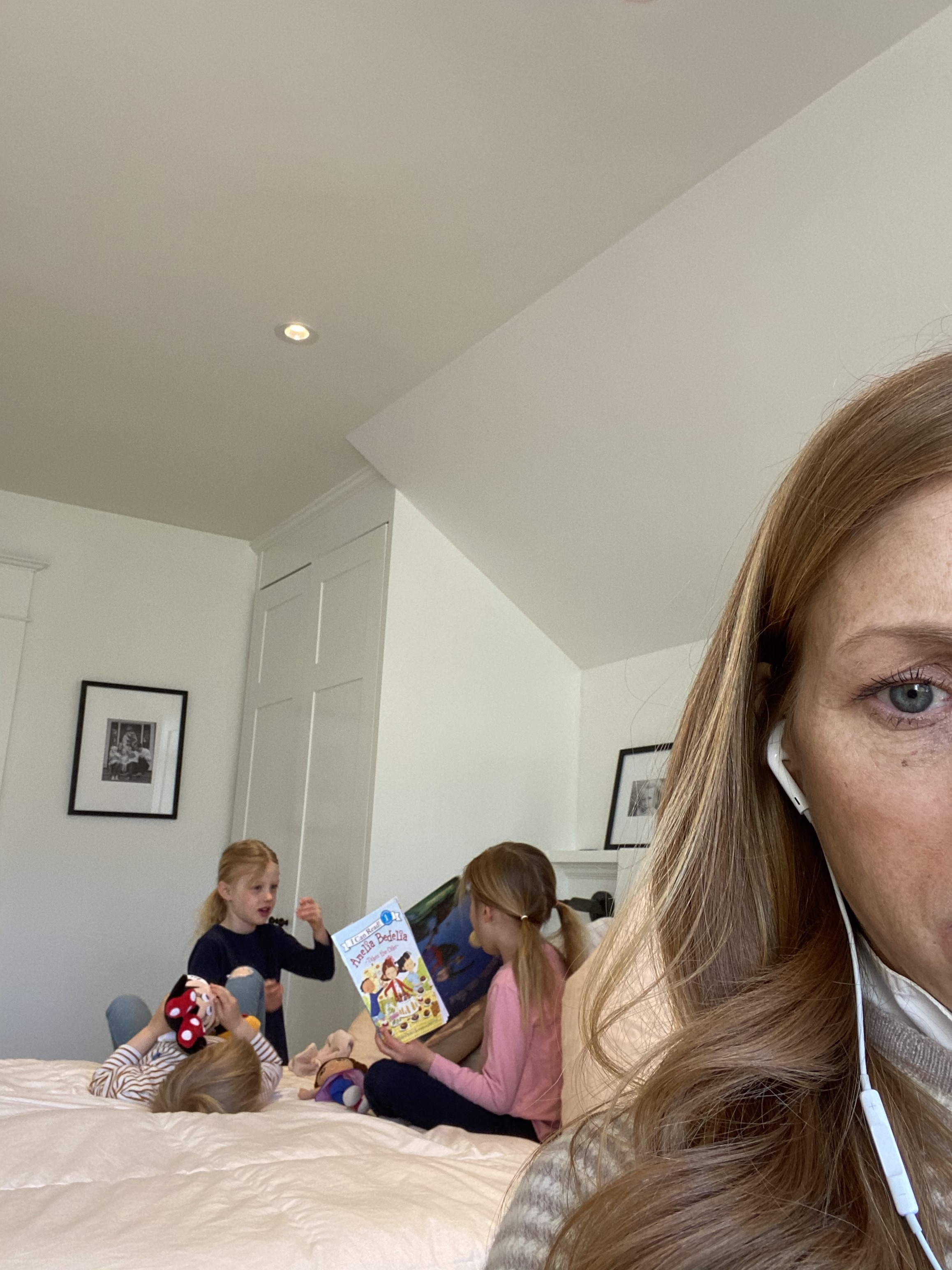 Martha Switzer on a conference call while three children play in the background