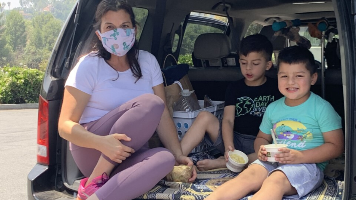 Photo of parent wearing a mask with two sons having lunch sitting on their trunk outside