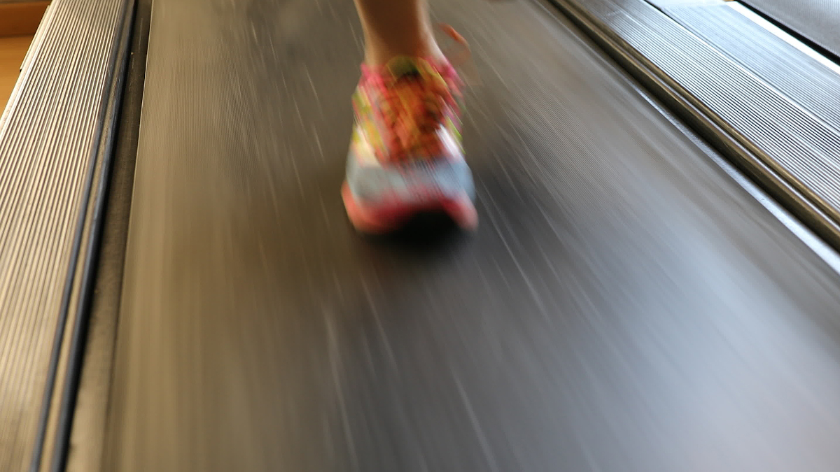 Running shoes closeup of athlete runner training. Woman feet in colorful shoes running on treadmill machine indoor. Fitness center training. Healthy lifestyle concept.