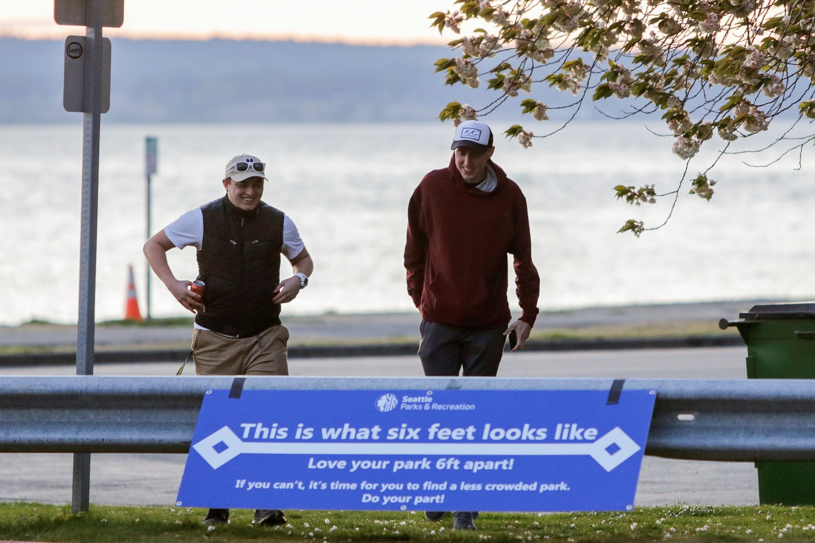 People walk past a sign at Golden Gardens Park asking people to stay six-feet apart after Seattle Mayor Jenny Durkan reopened parks that were closed Easter weekend as efforts continue to help slow the spread of the coronavirus disease (COVID-19) in Seattle, Washington, U.S. April 19, 2020.  REUTERS/Jason Redmond