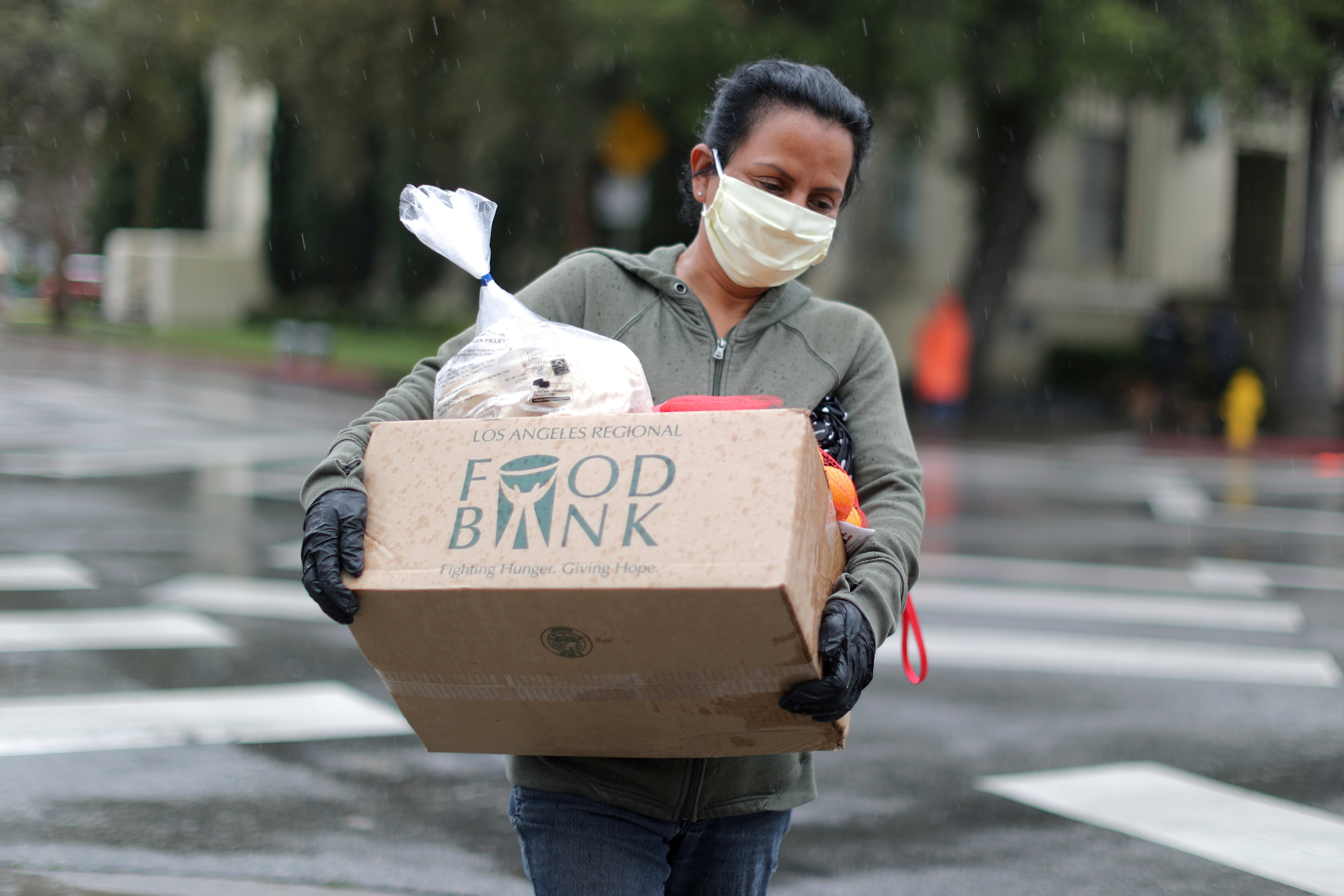 FILE PHOTO: A woman carries away fresh food at a Los Angeles Regional Food Bank giveaway of 2,000 boxes of groceries, as the spread of the coronavirus disease (COVID-19) continues, in Los Angeles, California, U.S., April 9, 2020.  REUTERS/Lucy Nicholson/File Photo