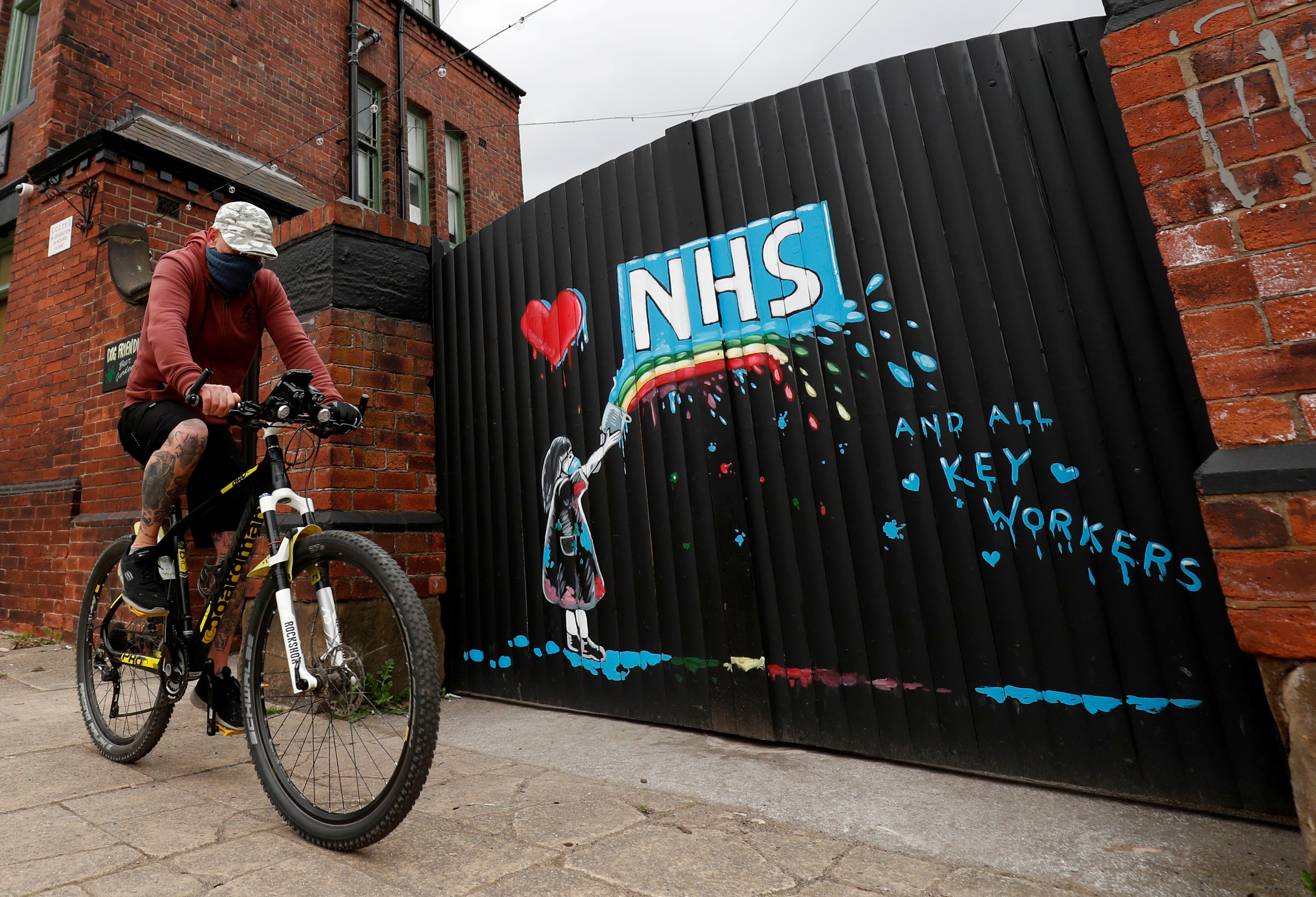 A cyclist rides past a mural in tribute to the NHS painted by artist Rachel List on the gates of Hope & Anchor pub in Pontefract, as the spread of the coronavirus disease (COVID-19) continues, Pontefract, Britain, April 4, 2020. REUTERS/Lee Smith