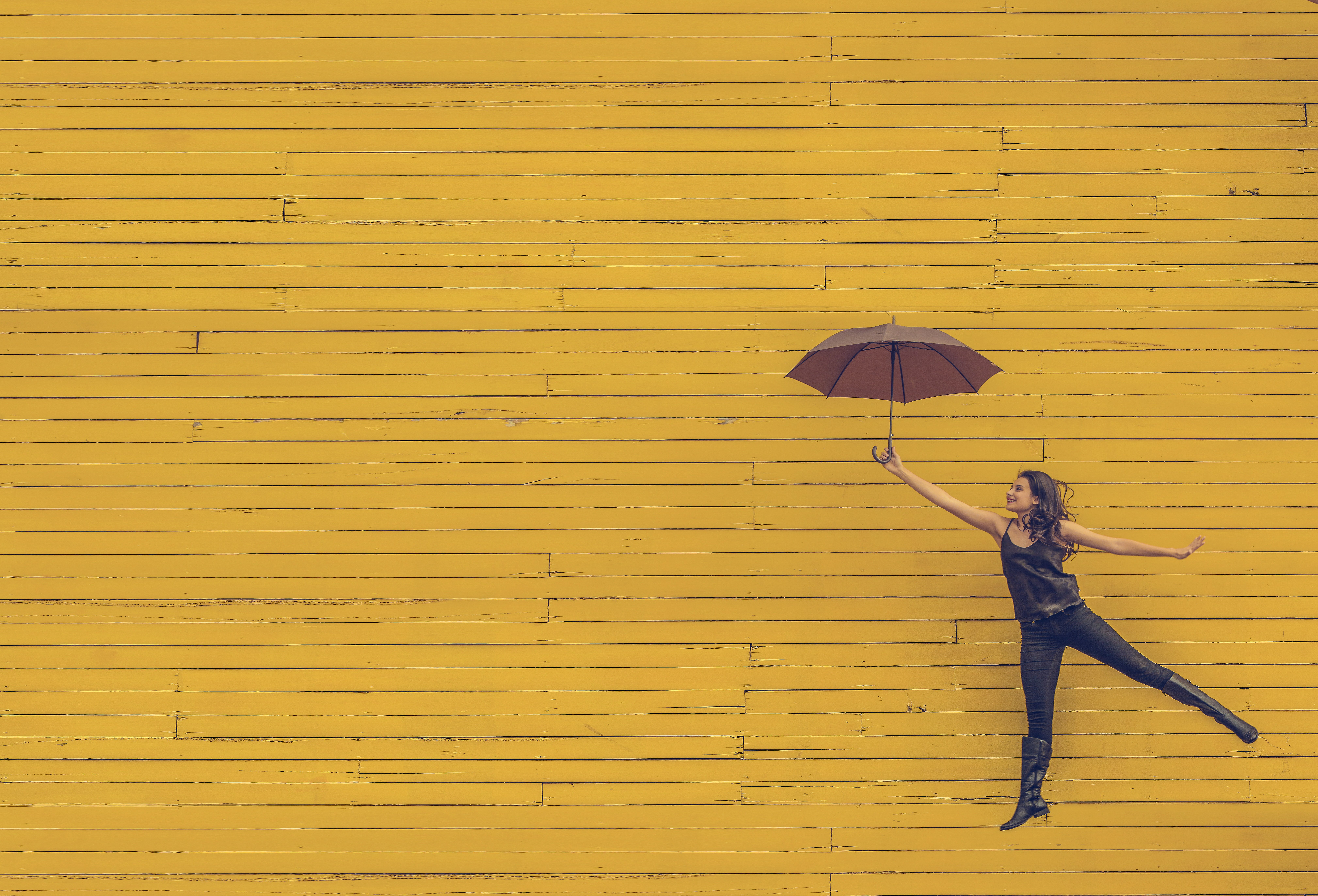 Girl holding an umbrella in front of yellow wall