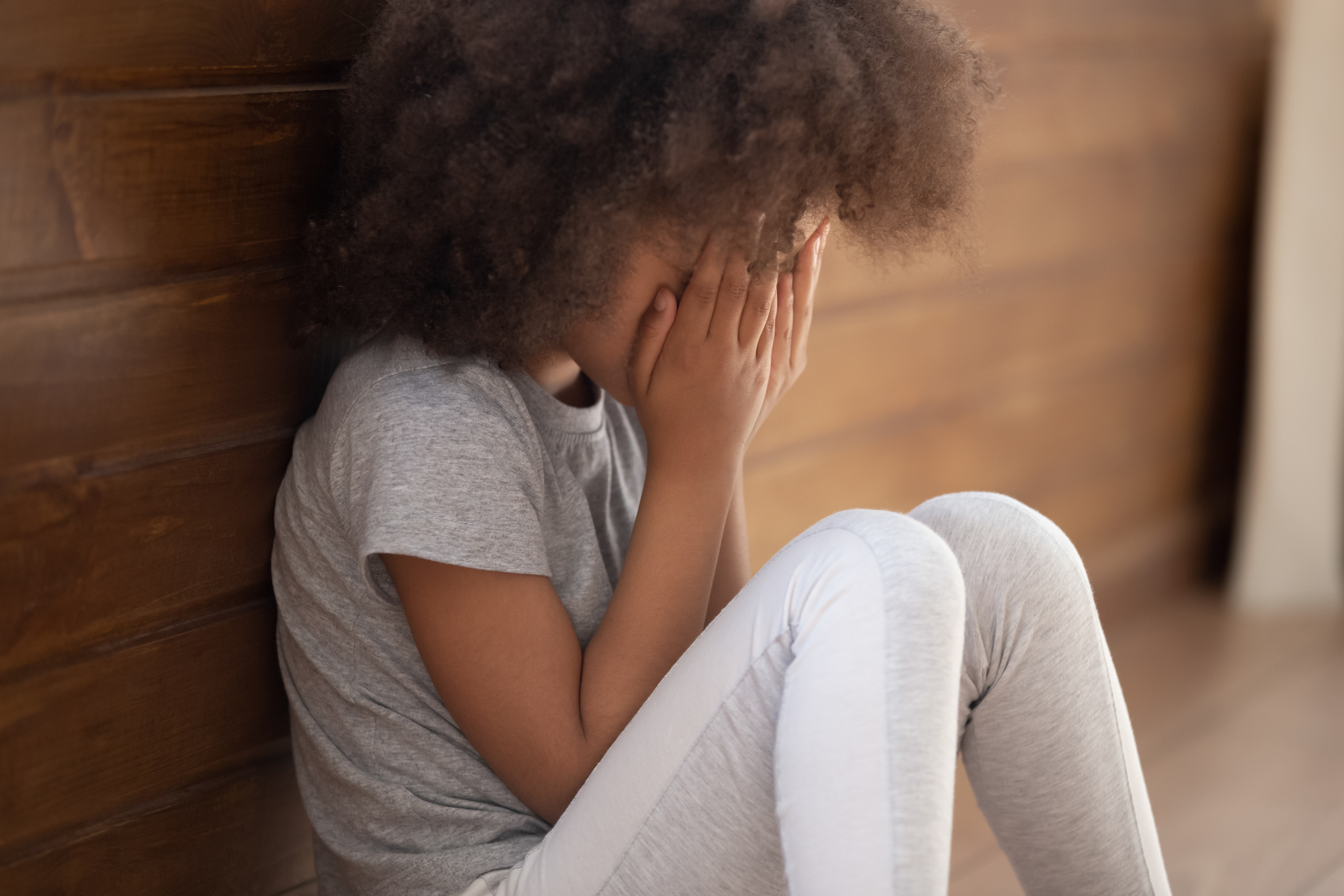 Upset small african american child girl crying covering face with hands sitting alone on floor, sad lonely orphan kid being bullied abused feeling stressed or scared, children violence abuse concept