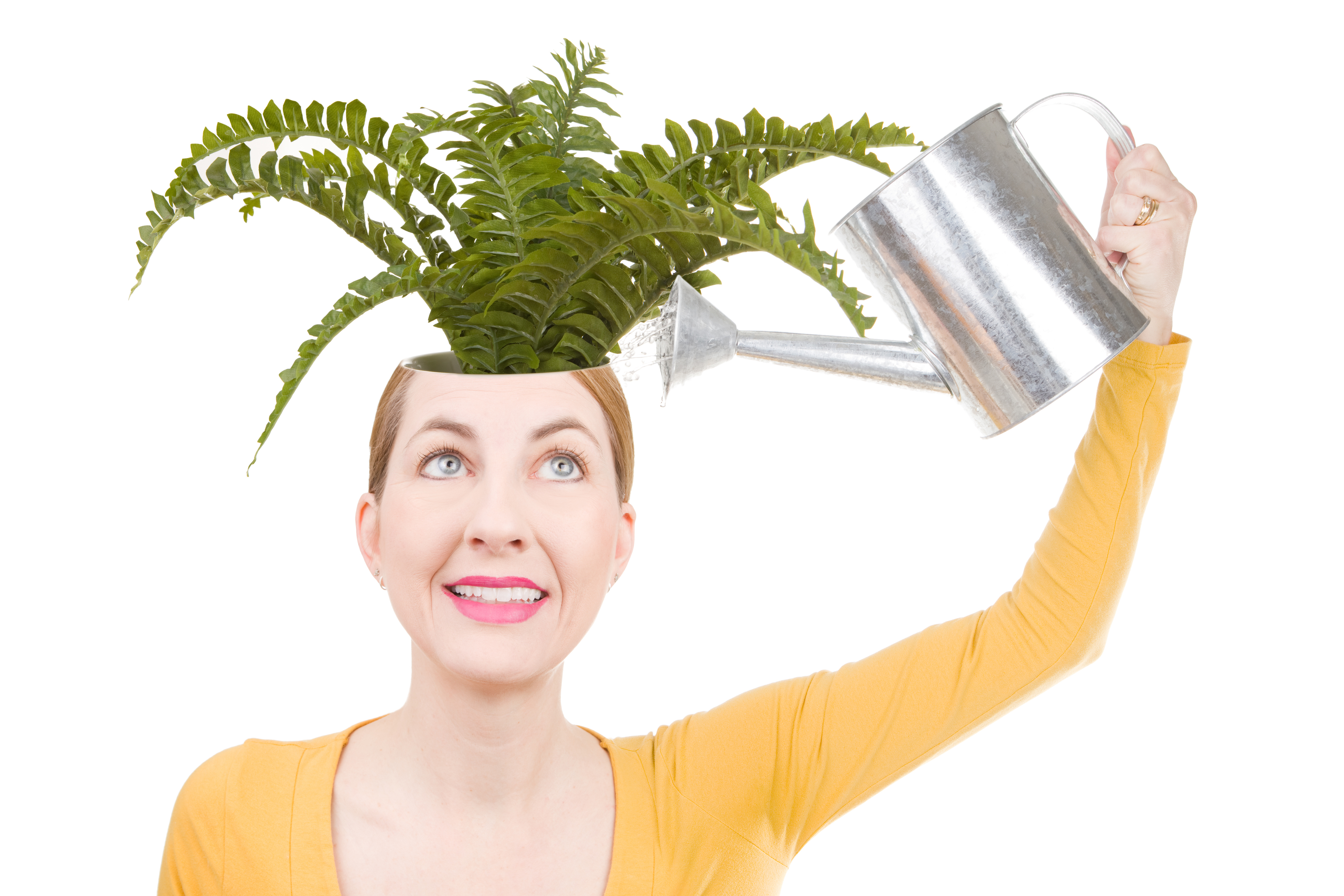 A conceptual image of a woman watering a plant that is growing from inside her head.