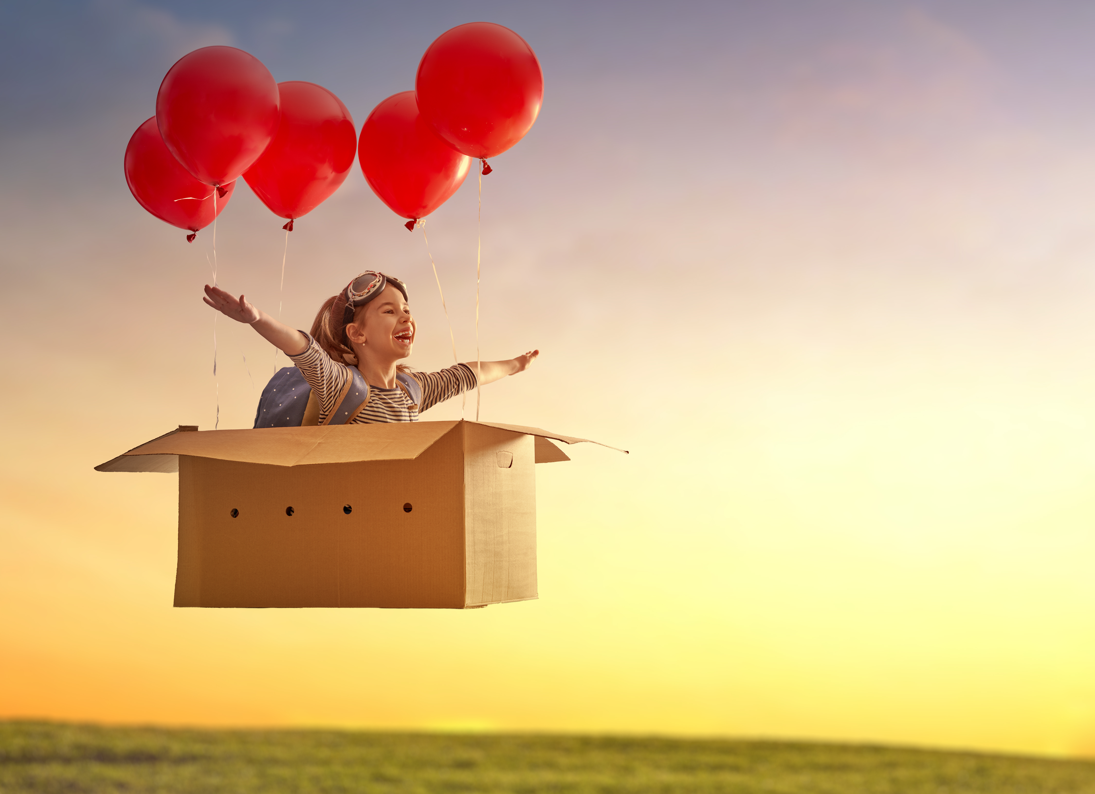 Dreams of travel! Child is flying in cardboard box with air balloons.
