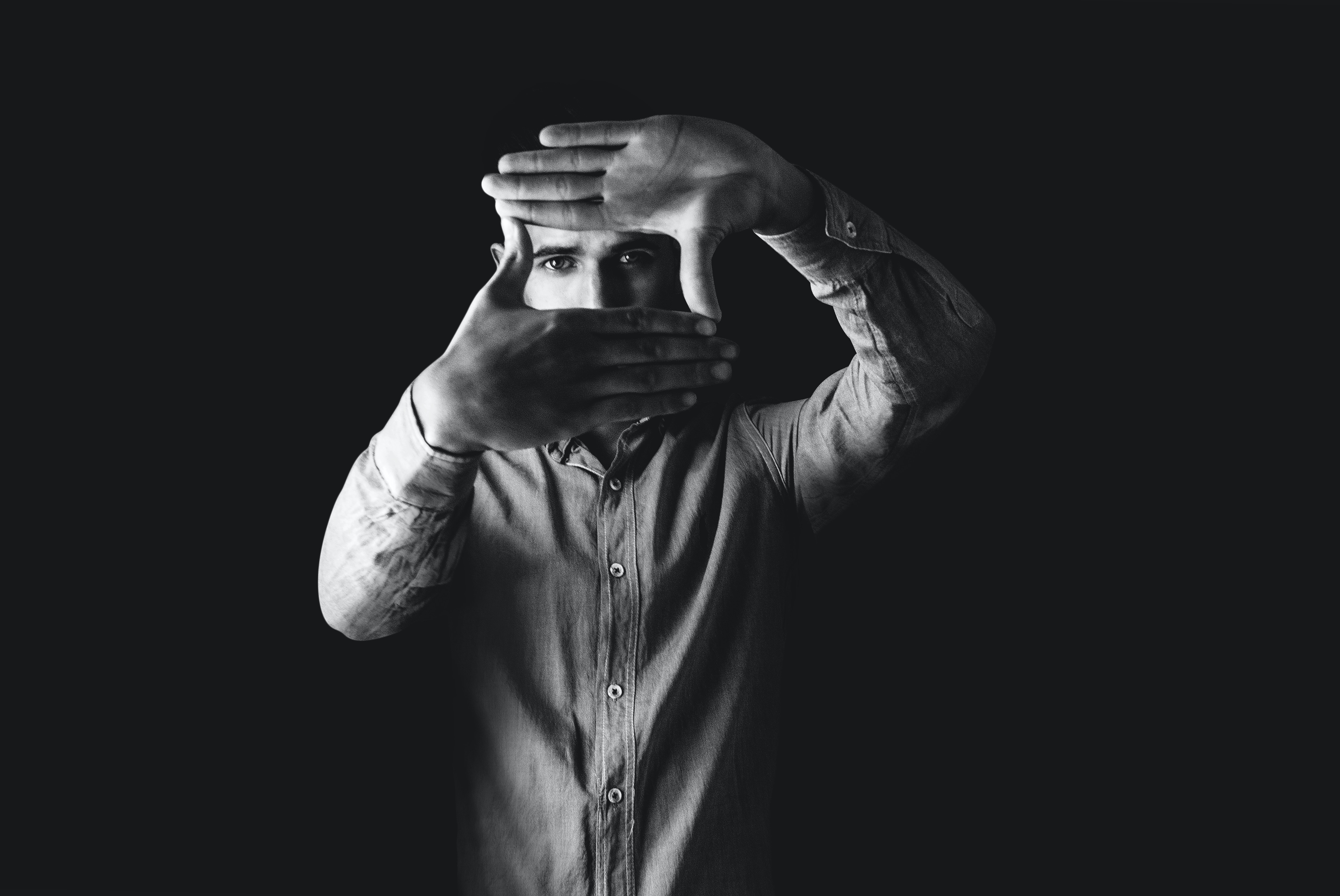 Black and white photo of man looking into the camera through a square he made with his hands