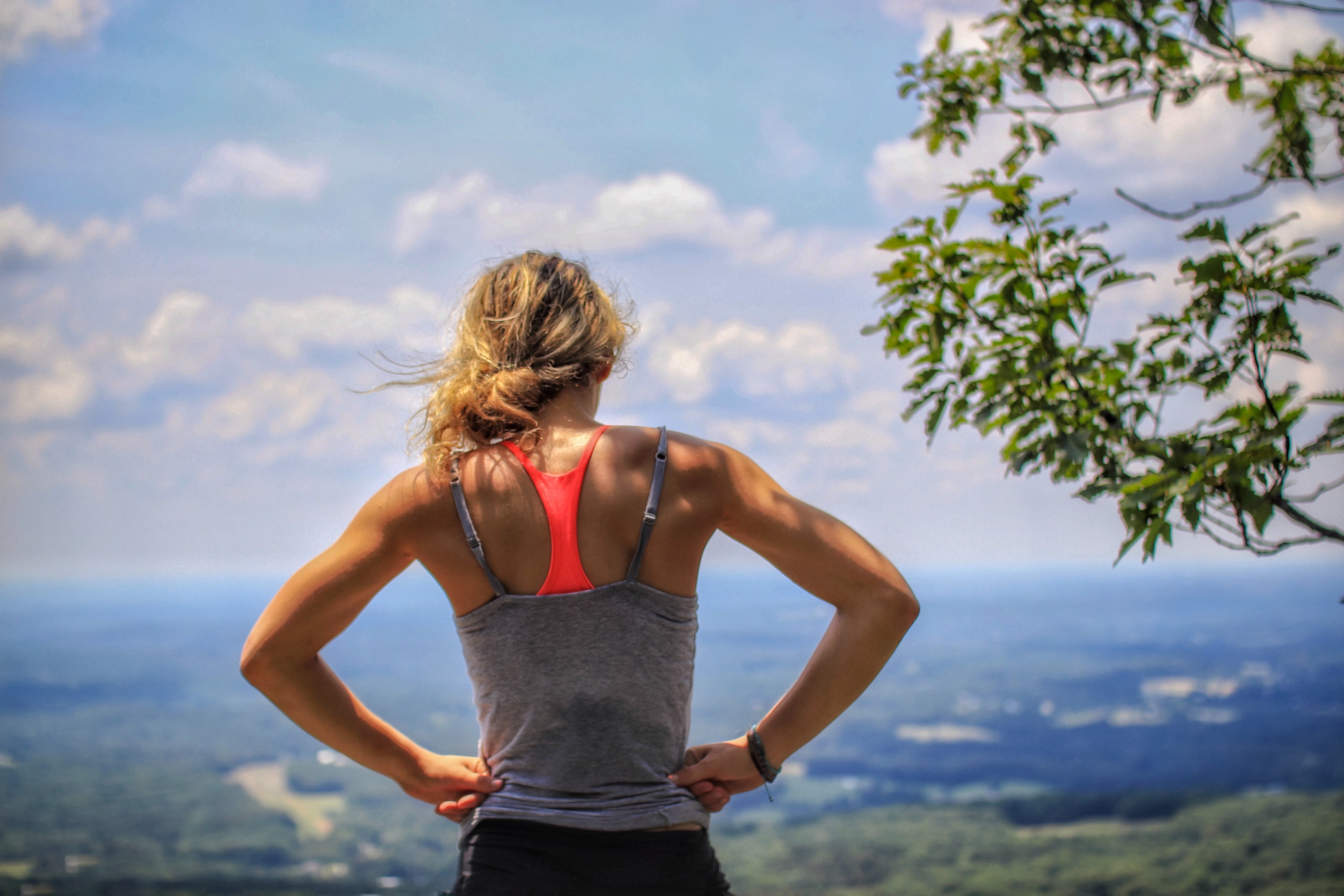 Woman standing on top of mountain looking at city below