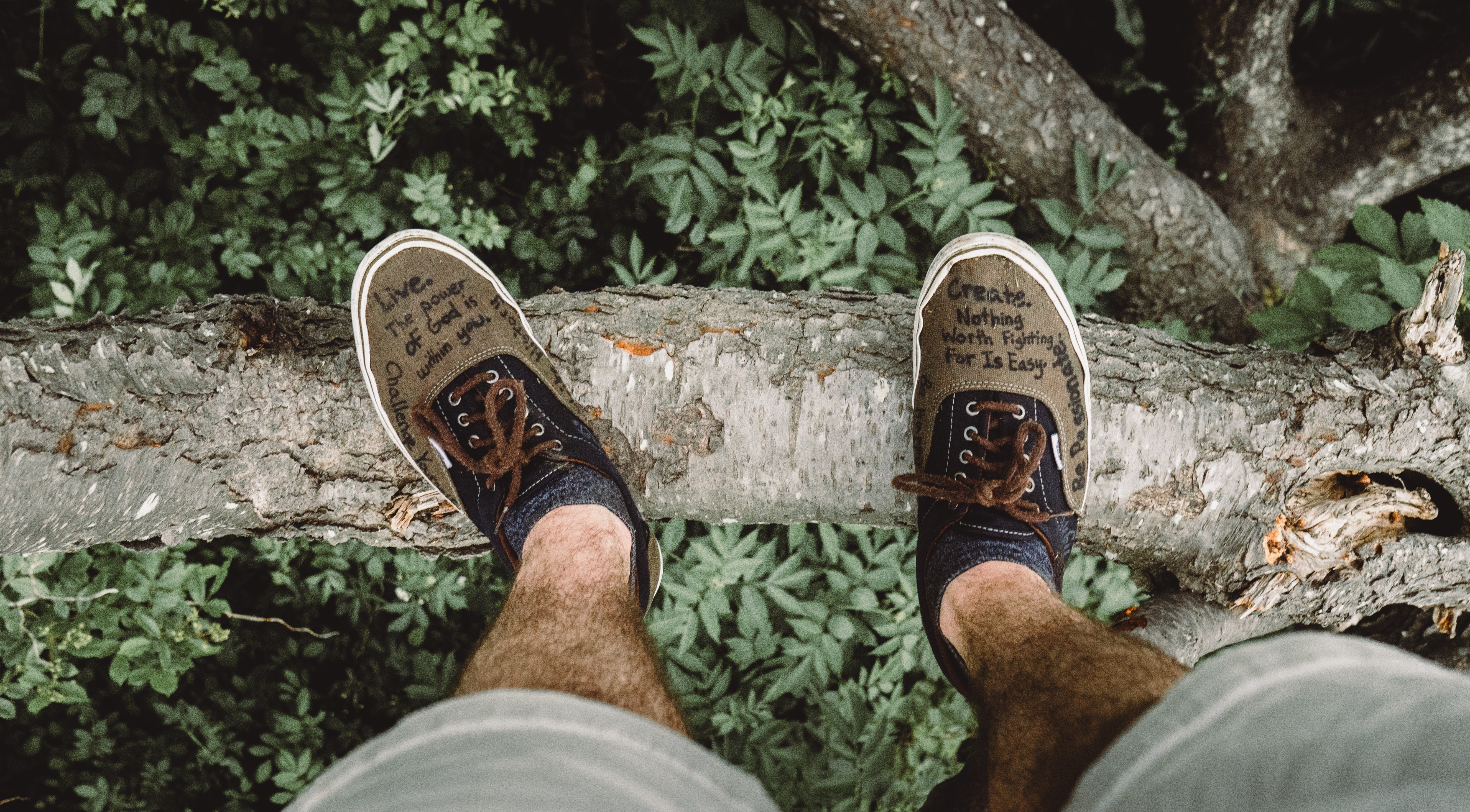 Man legs standing on the edge of a cliff with motivational quotes on his shoes.
