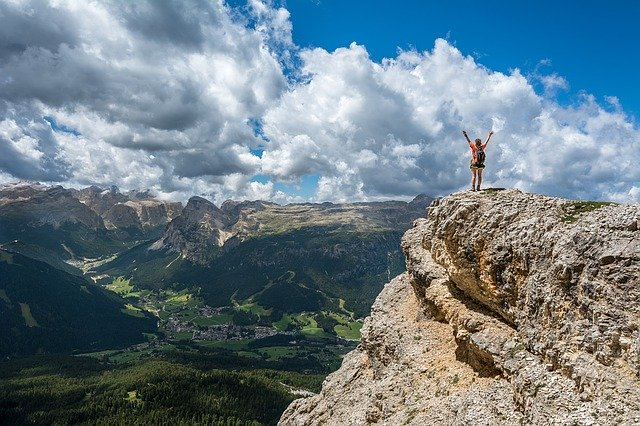 person standing on the edge of a mountain