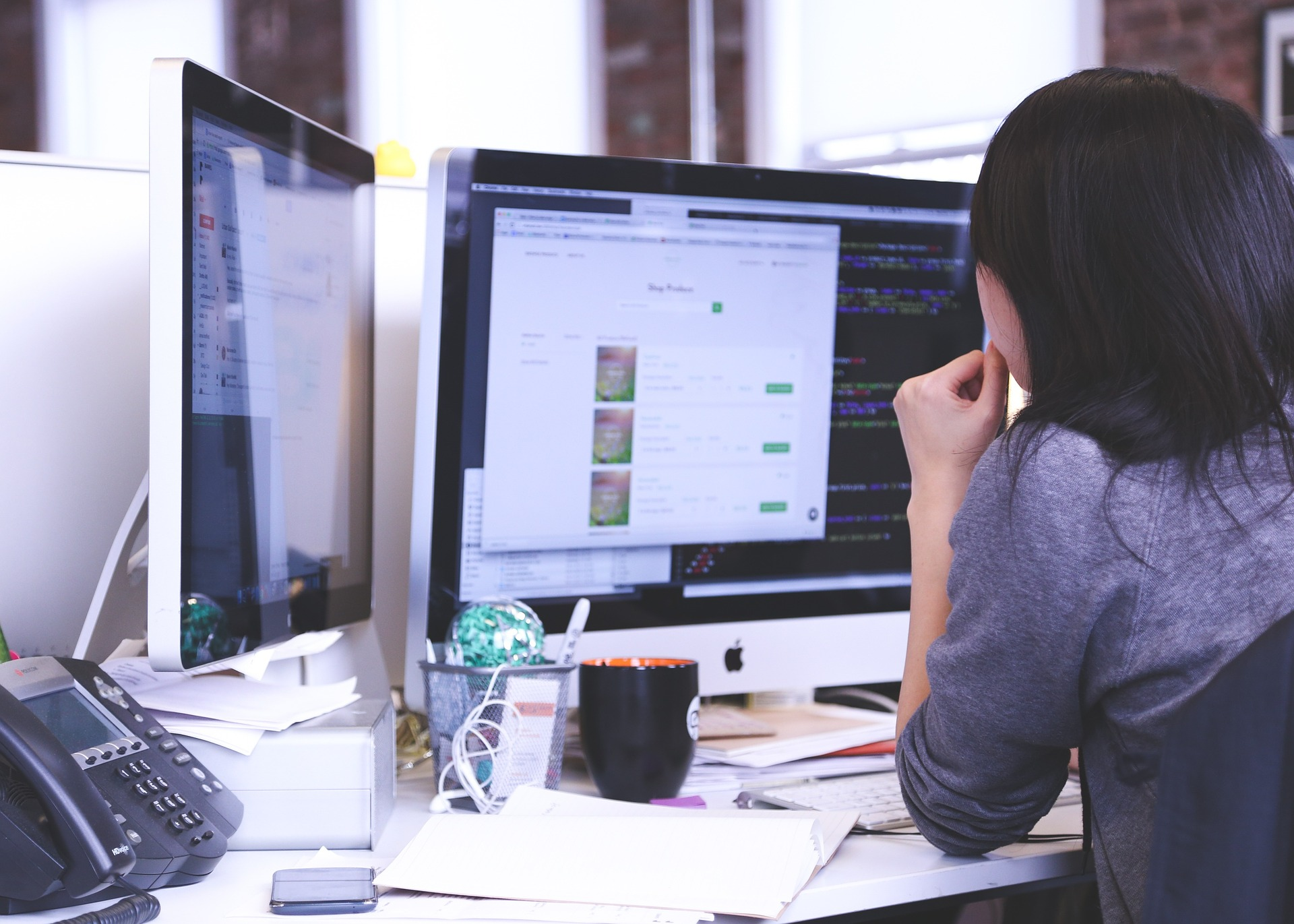 Woman working at a desk with dual monitors