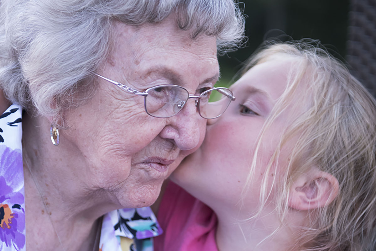 grandma with great granddaughter giving her a kiss on the cheek