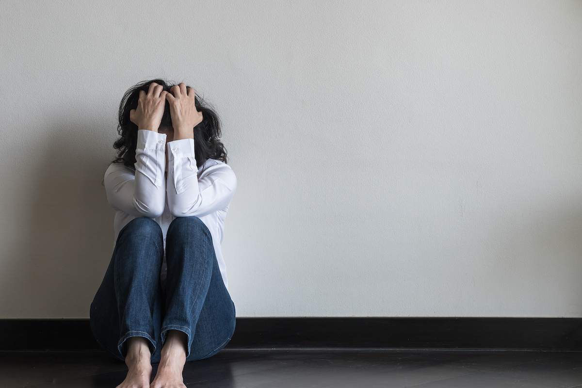 Anxiety disorder menopause woman, stressful depressed emotional person with mental health illness, headache and migraine sitting feeling bad sadly with back against wall on the floor in domestic home