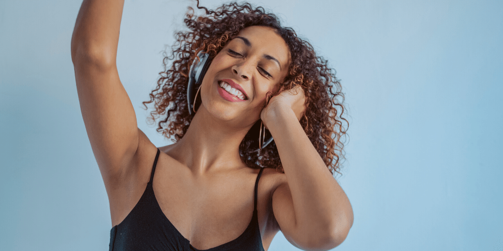 woman with headphones dancing a happy dance