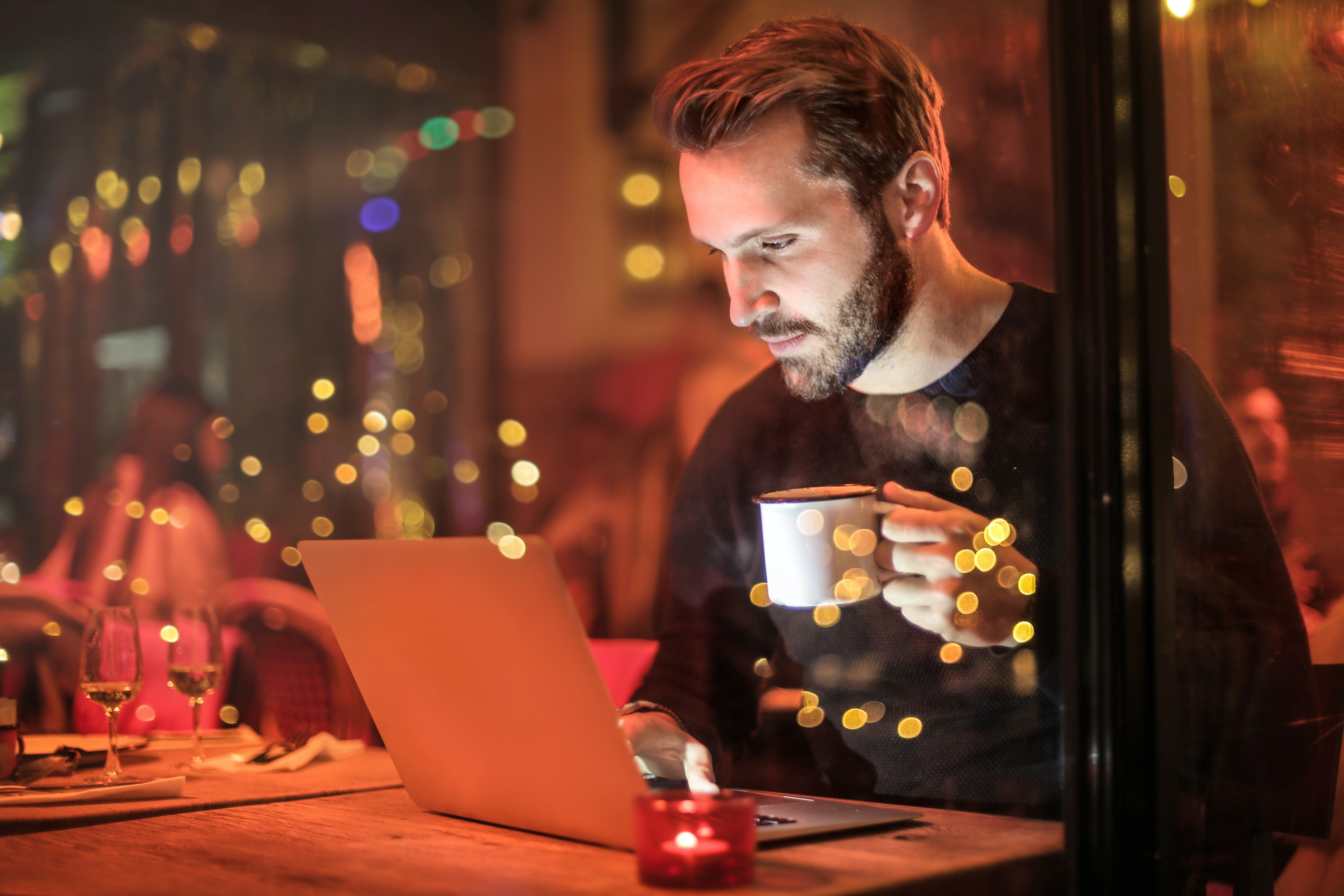 Man in a black sweater holding a cup of coffee and staring down at his computer.