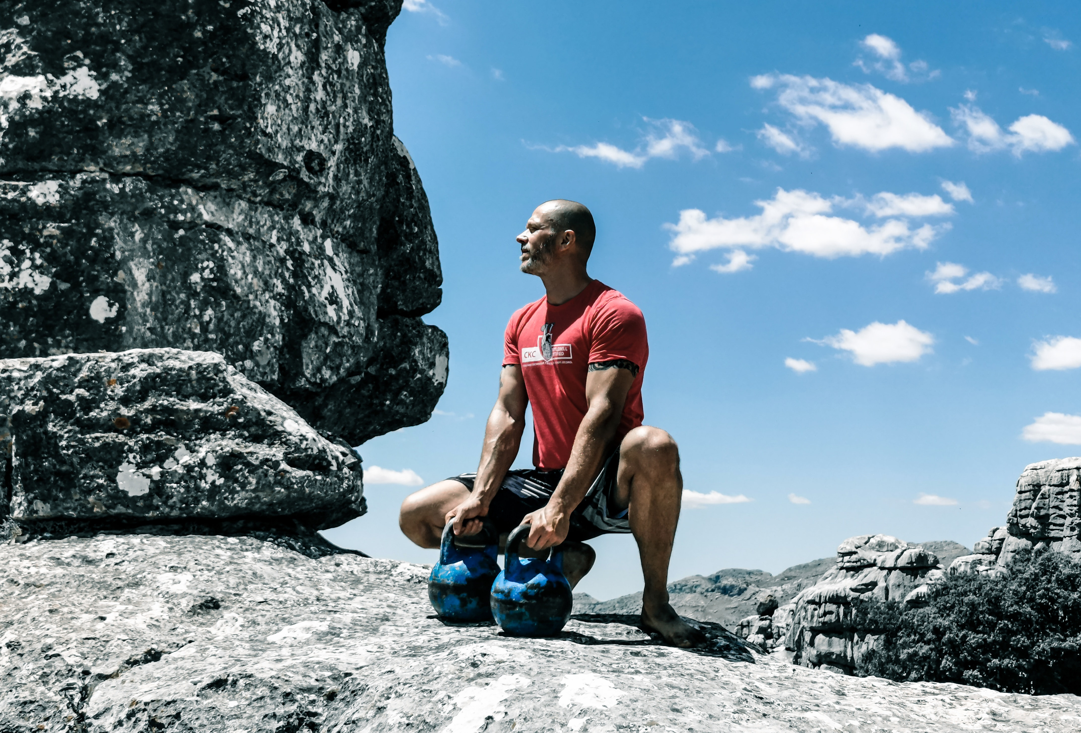 Man in red shirt squatting down on the edge of a cliff holding 2 blue kettle bell weights