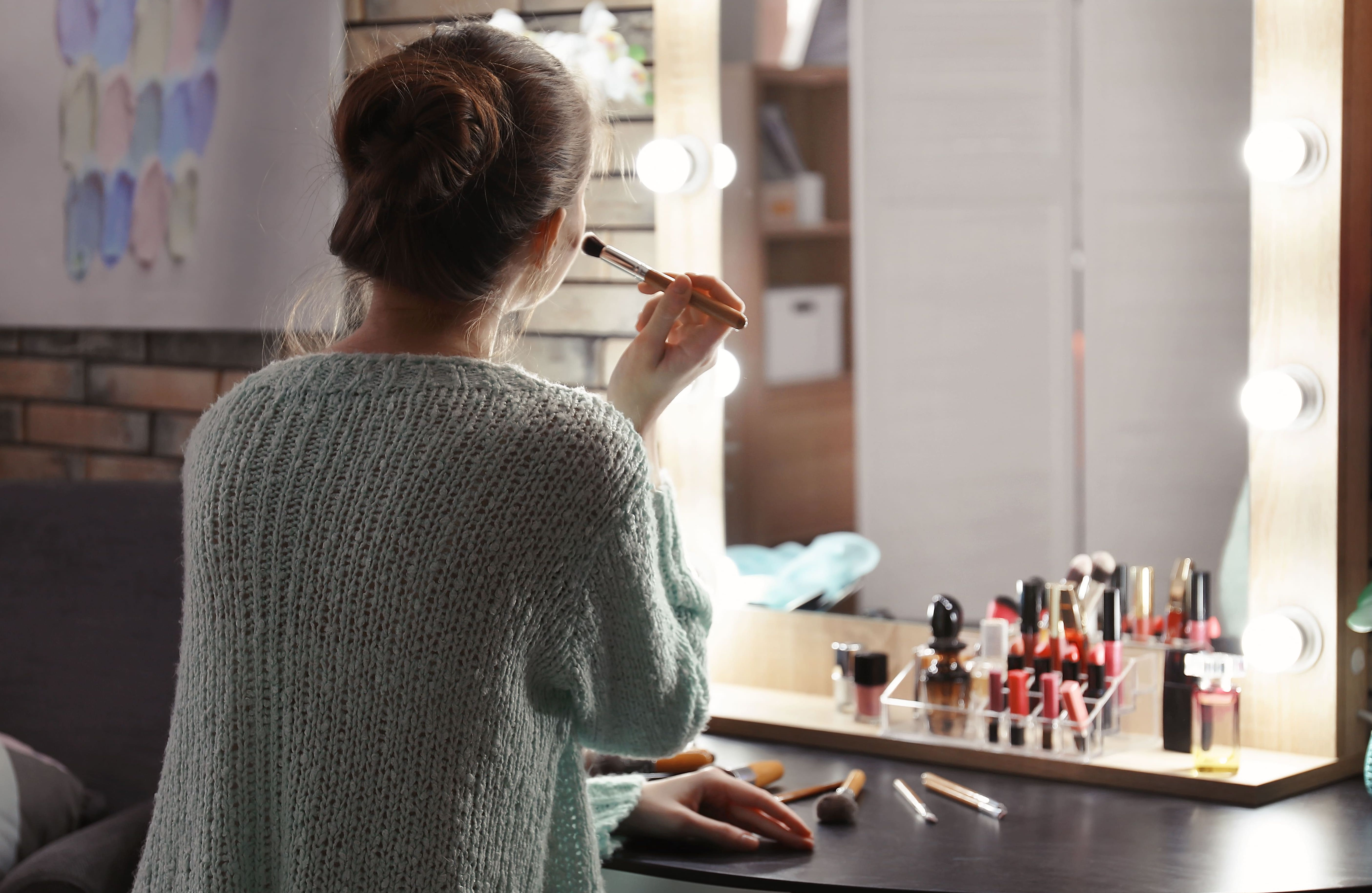 Woman sat at a dressing table putting makeup on in front of the mirror