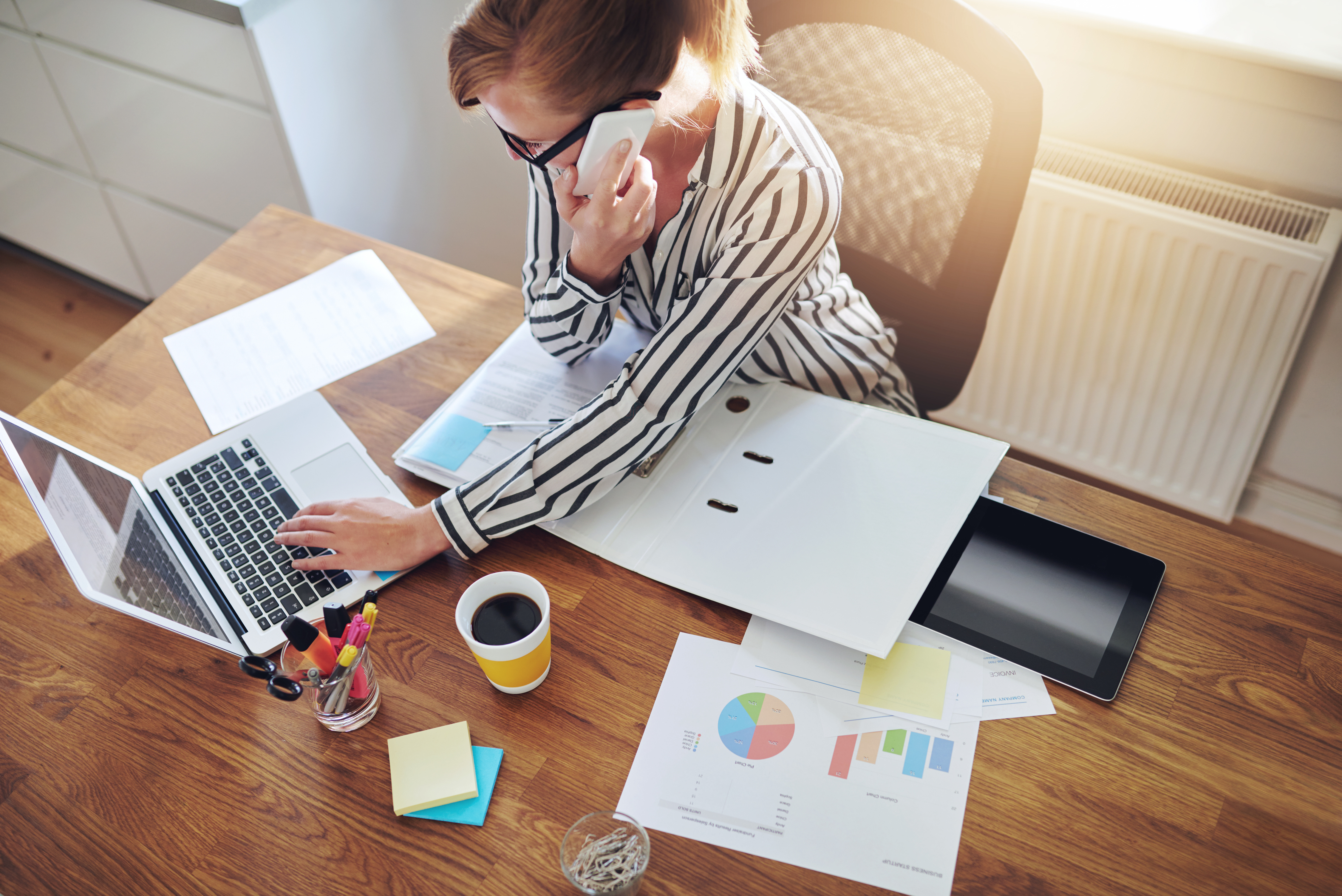 Successful businesswoman with an e-business working from an office at home telemarketing and taking orders over the phone or consulting with clients, high angle view