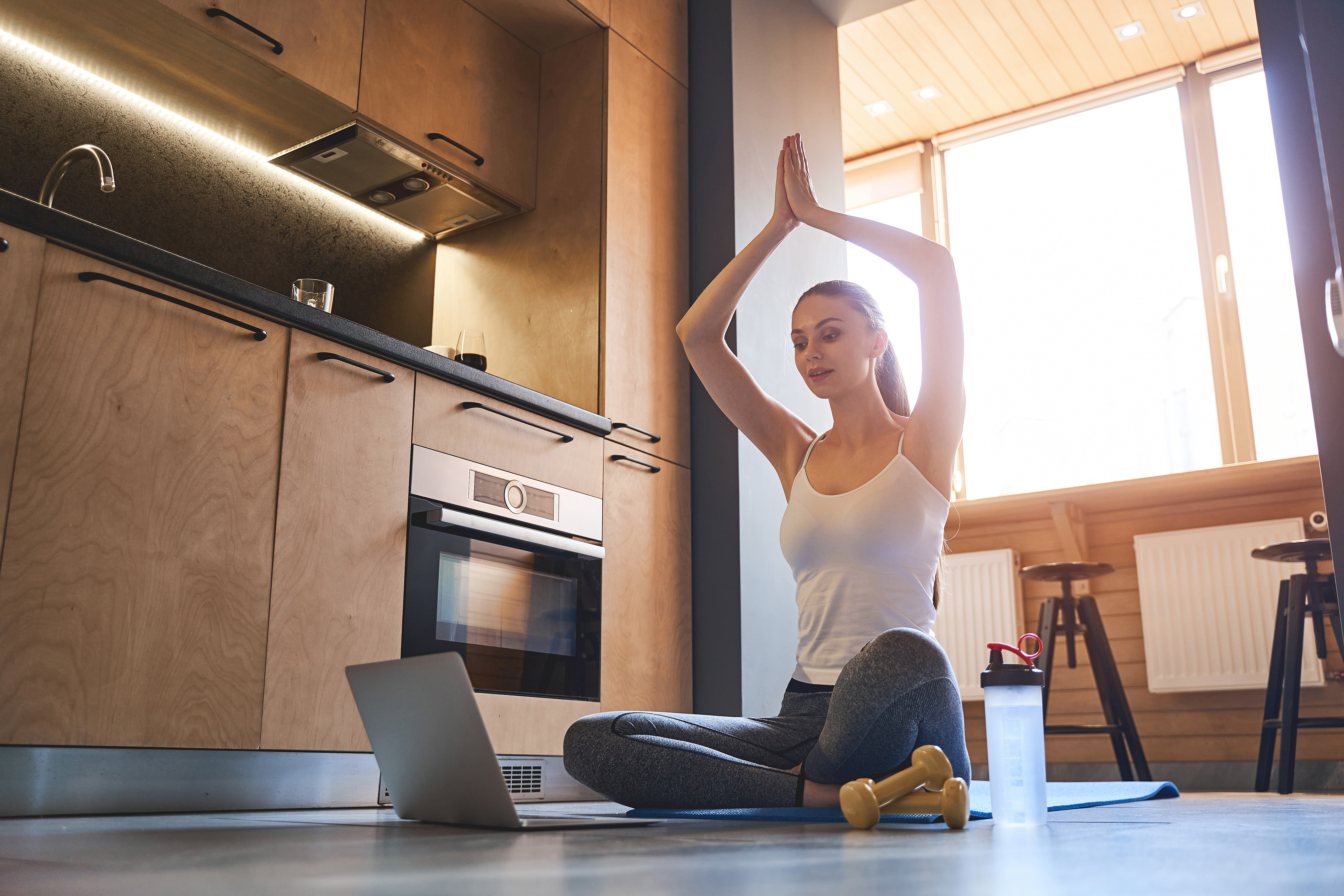Serious slim young woman practicing yoga on a mat in front of her online audience