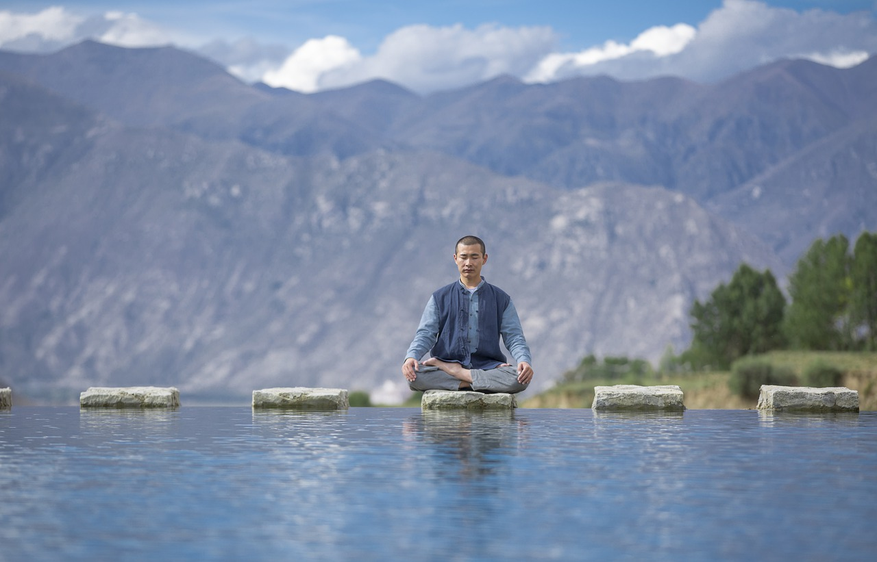 A person meditating on a stepping stone above a body of water