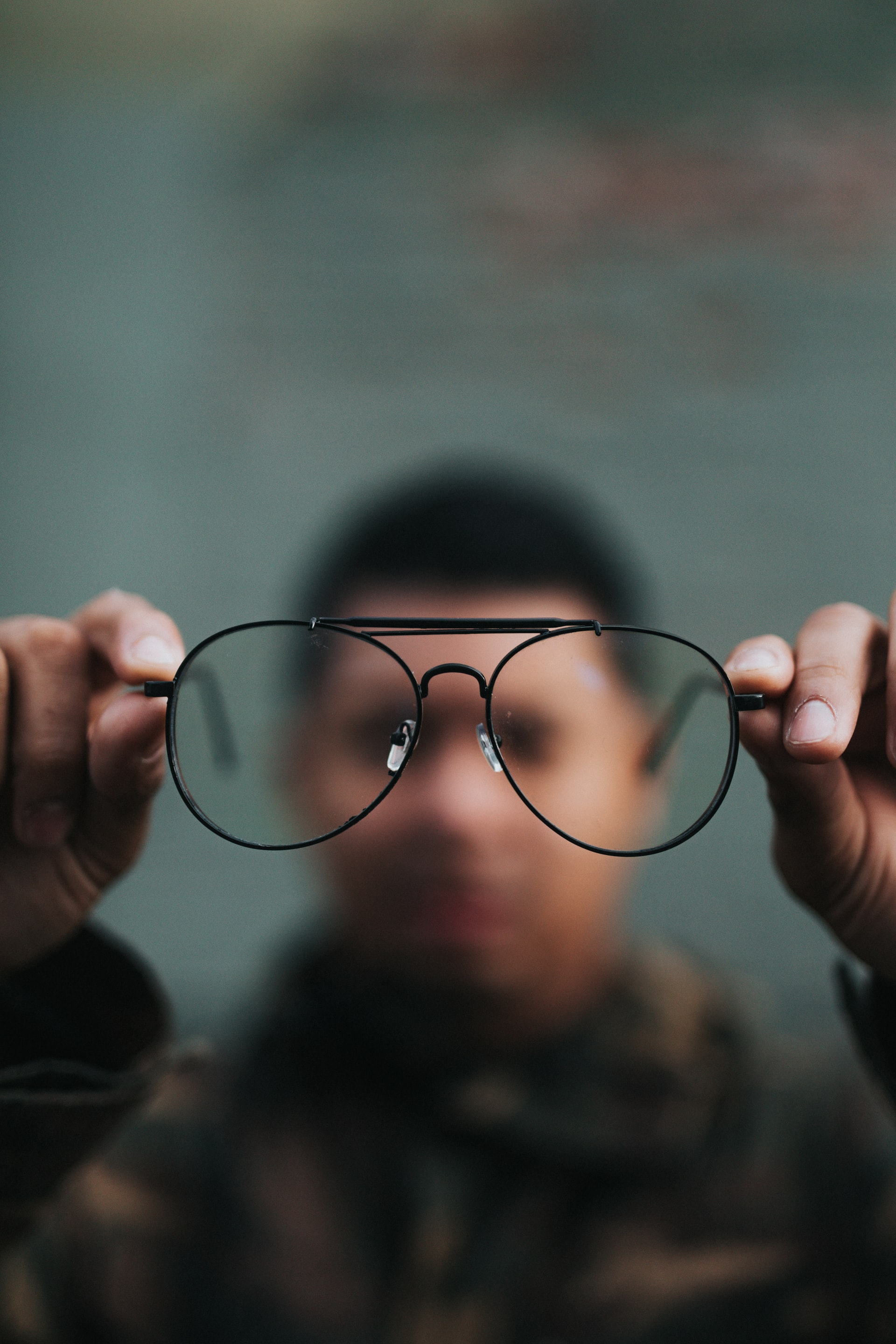 Man holding up glasses to inspect.