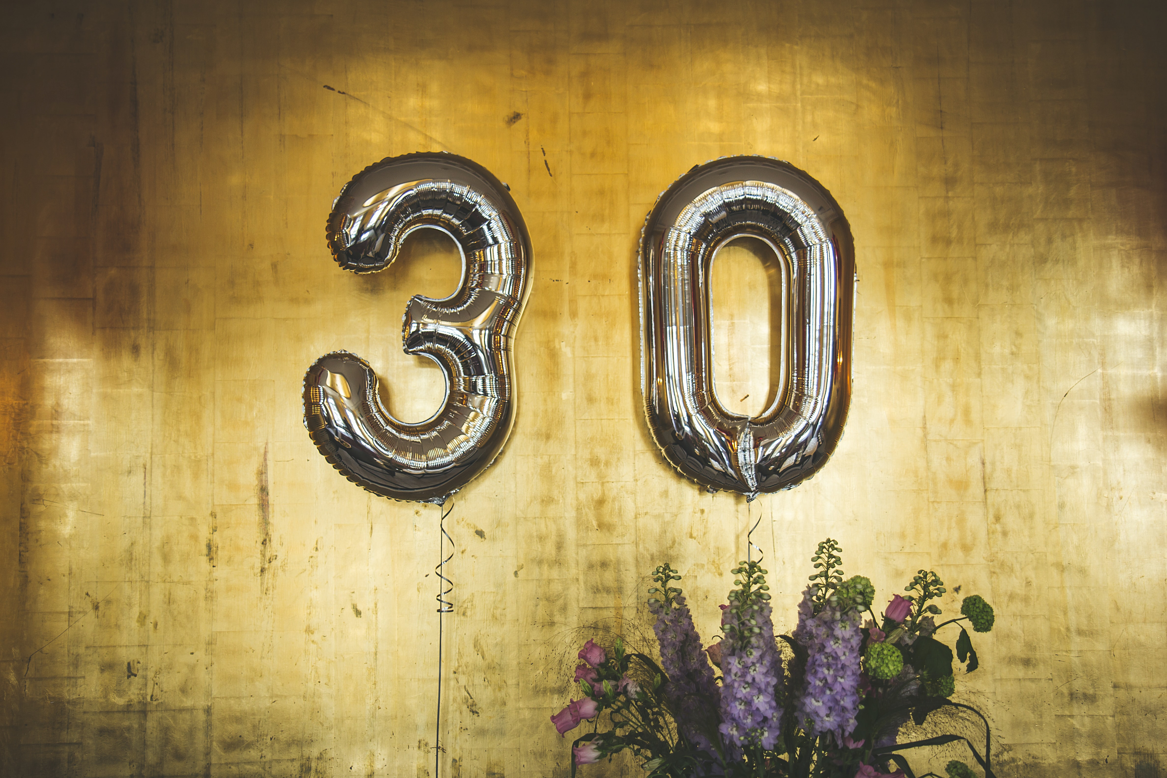 Numbered gold balloons that spell out the number 30 against a wooden backdrop and purple flowers.