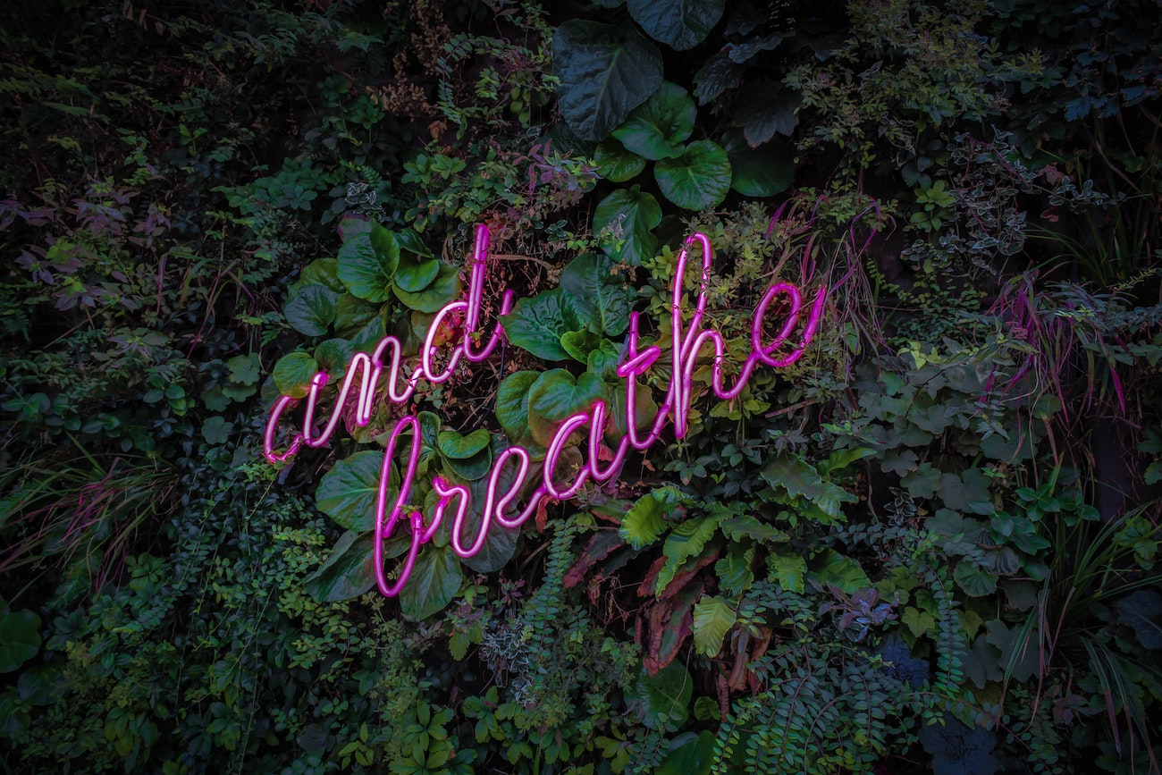 image of neon sign that says And Breathe