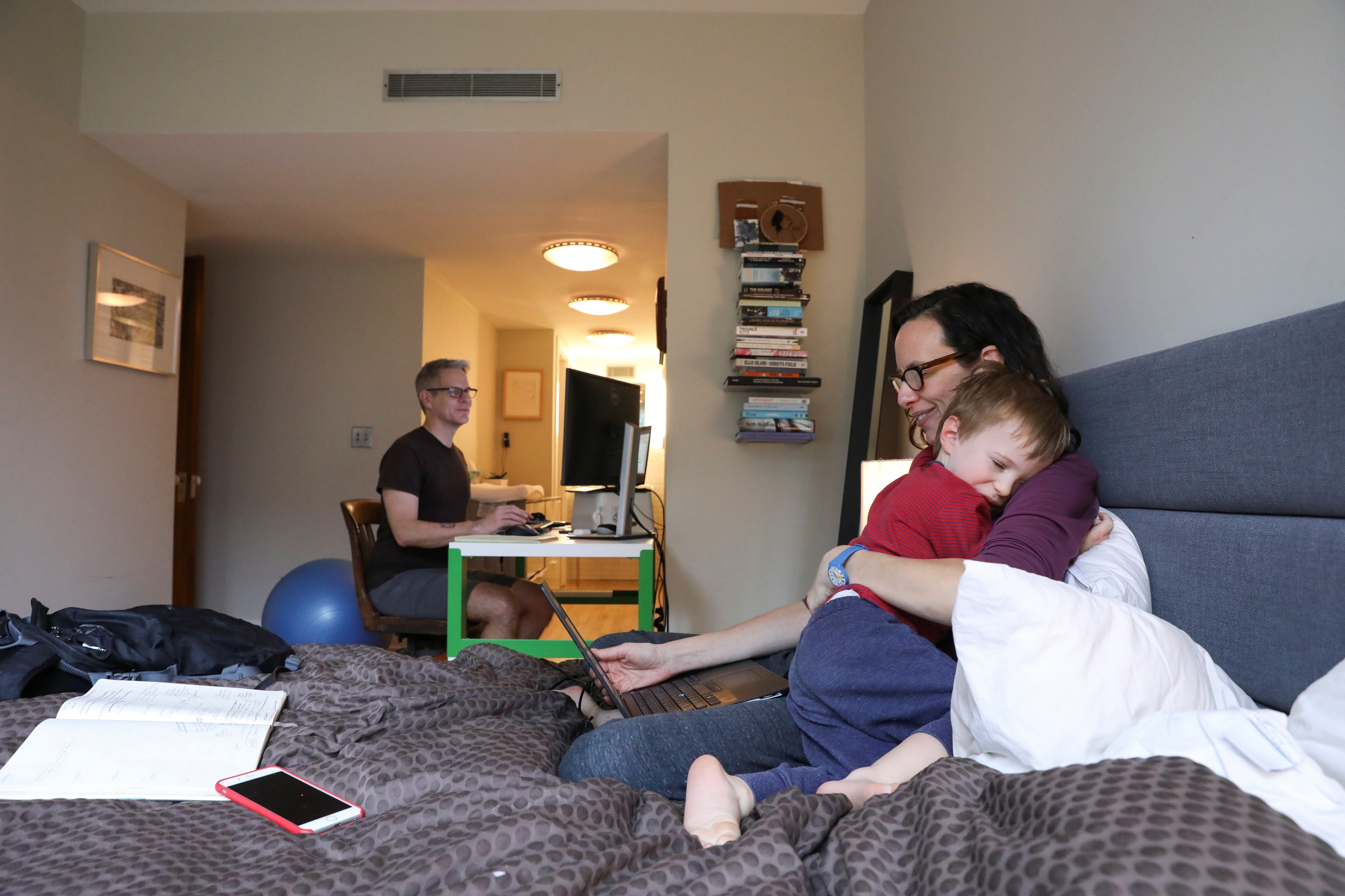 Naomi Hassebroek holds her son Felix while working with her husband Doug Hassebroek at their home, after New York State Governor Andrew Cuomo signed an executive order closing New York public schools statewide due to public health concerns over the rapid spread of coronavirus disease (COVID-19) in Brooklyn, New York, U.S., March 19, 2020. REUTERS/Caitlin Ochs