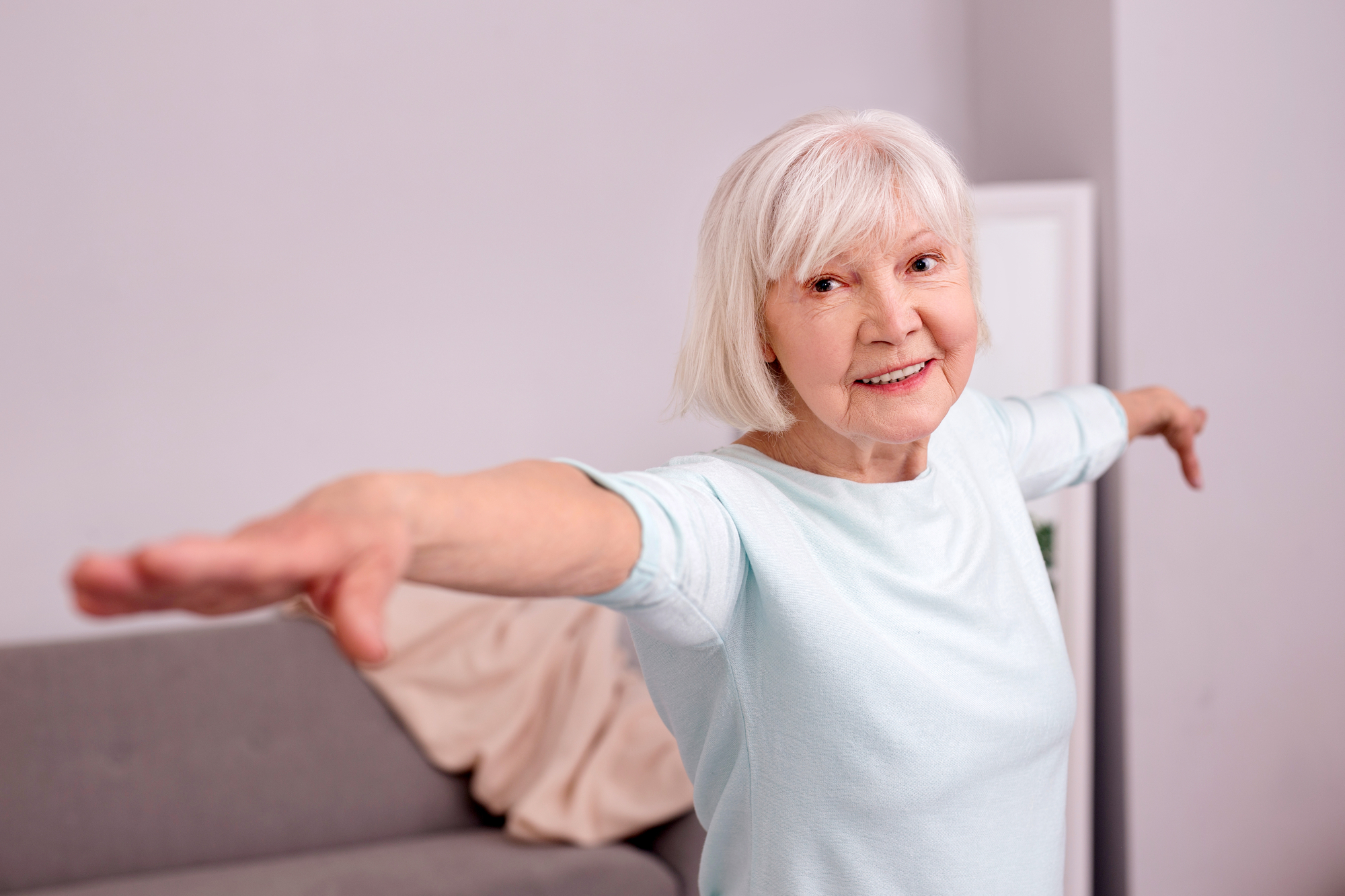 pleasant woman spreading arms wide and smiling