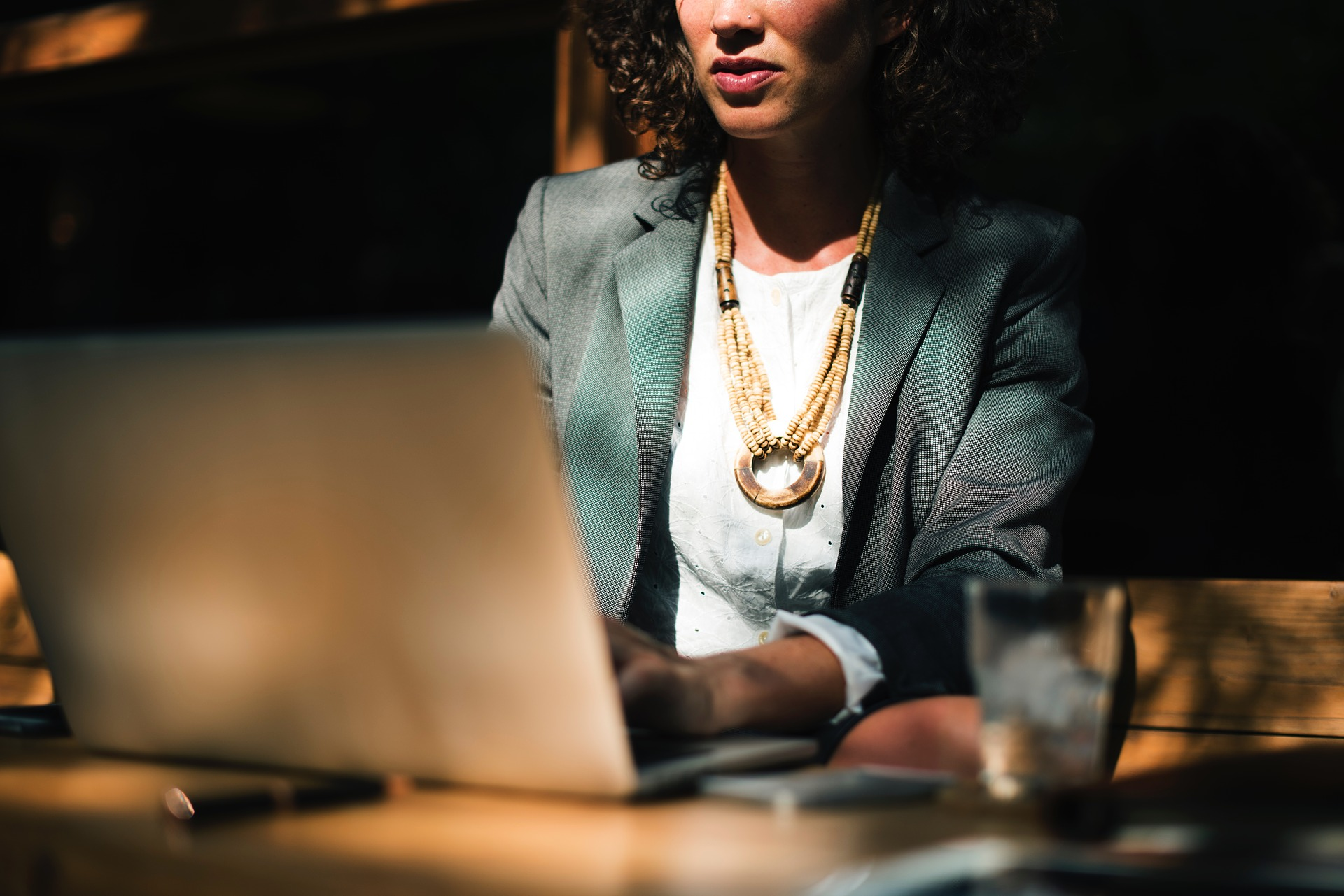 Woman in business casual attire working on a laptop