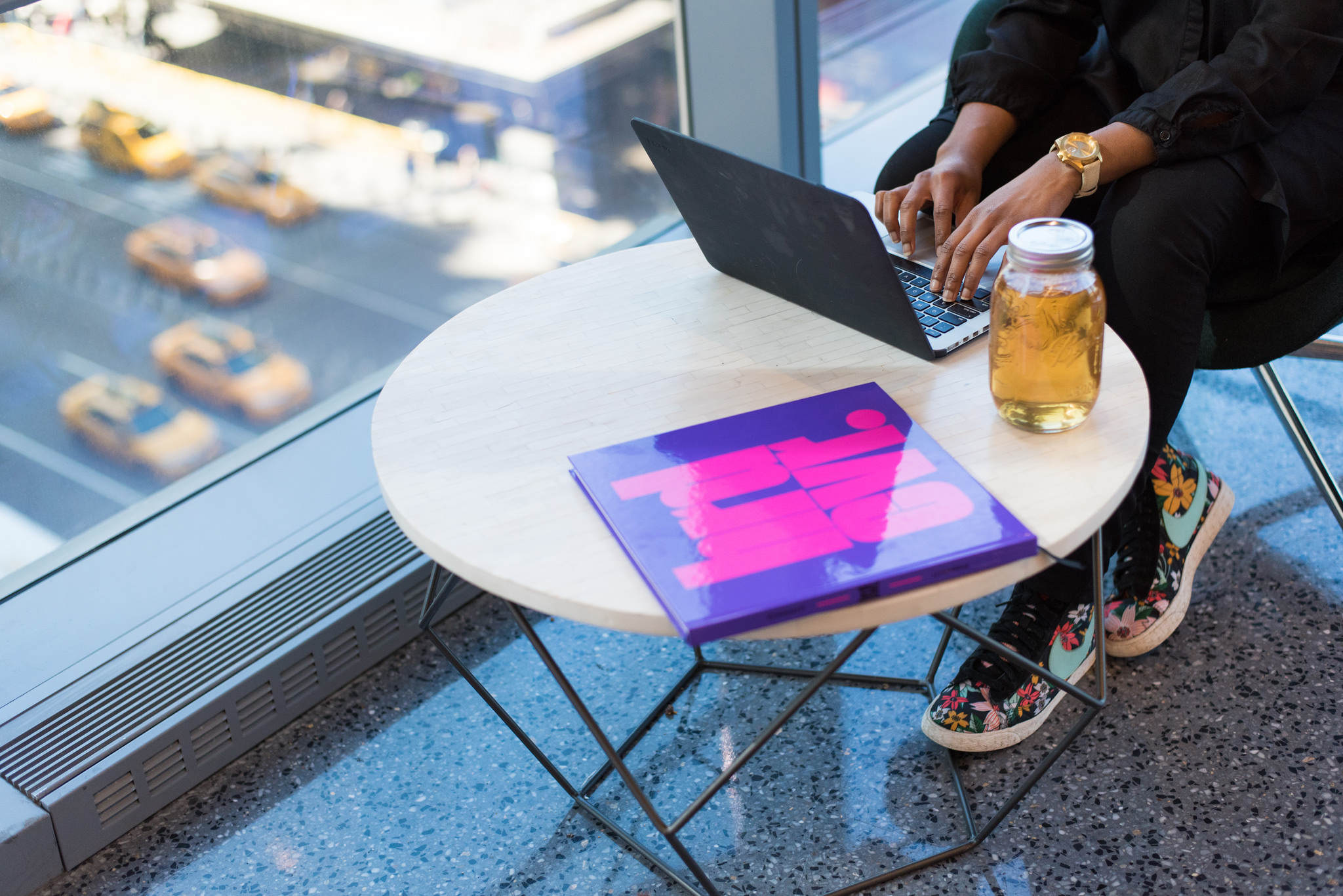 A black woman sits at a table with ice tea and her computer