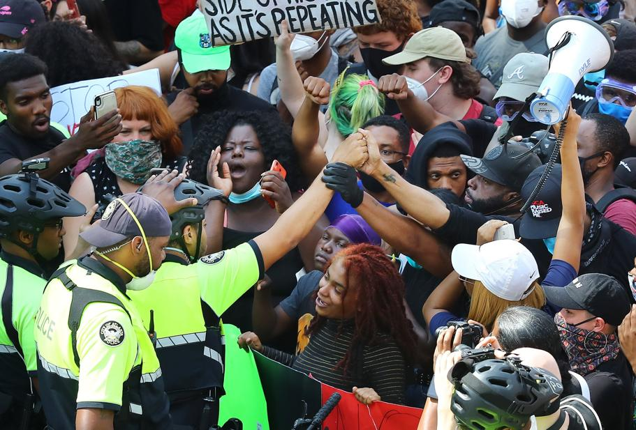 Atlanta Police Officer reaches out in solidarity with protestors outside of CNN Center, Tuesday, June 2, 2020 (Curtis Compton/Atlanta Journal-Constitution via AP)