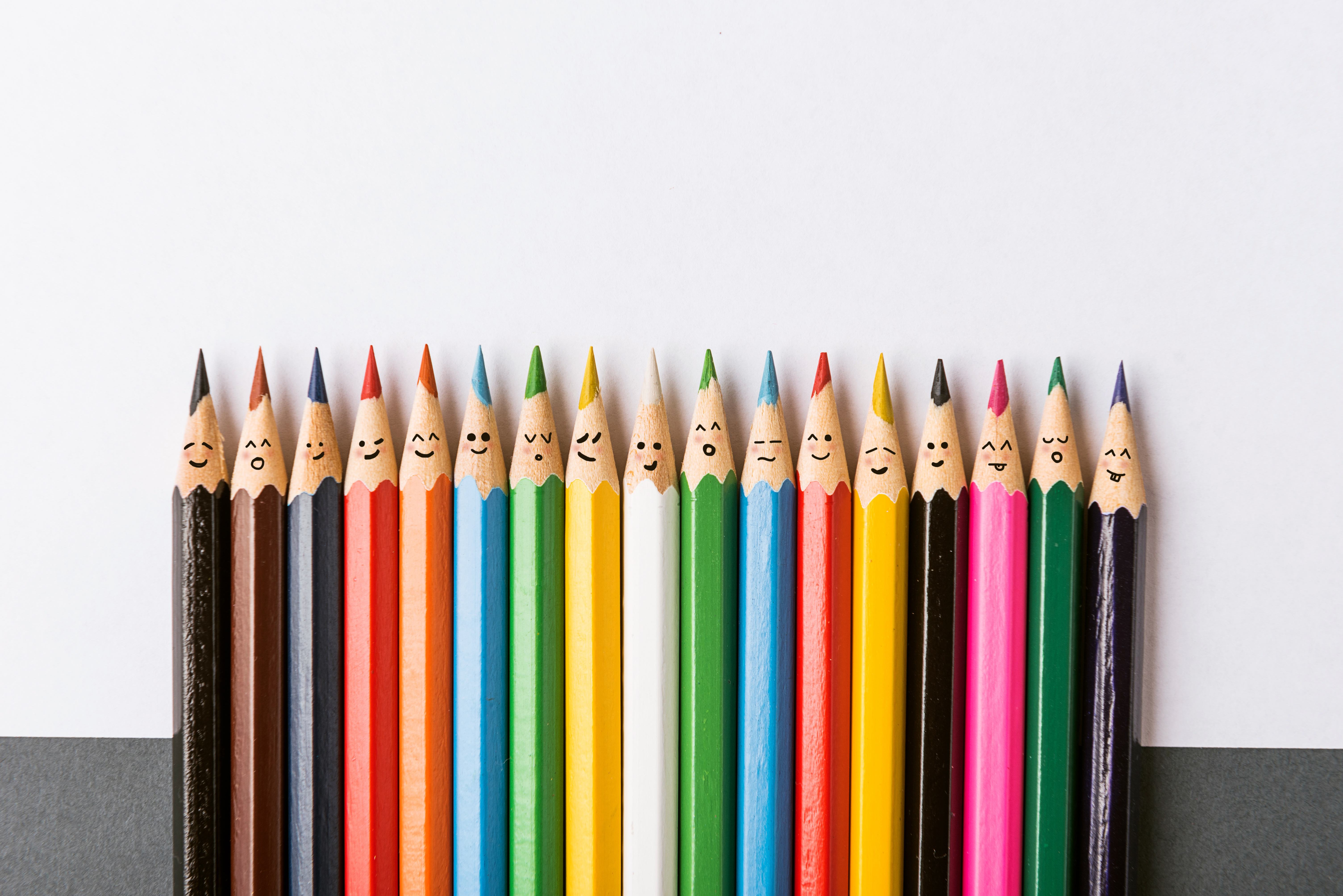 Color pencils with faces painted on them. the concept of a multinational family and equality in the world.