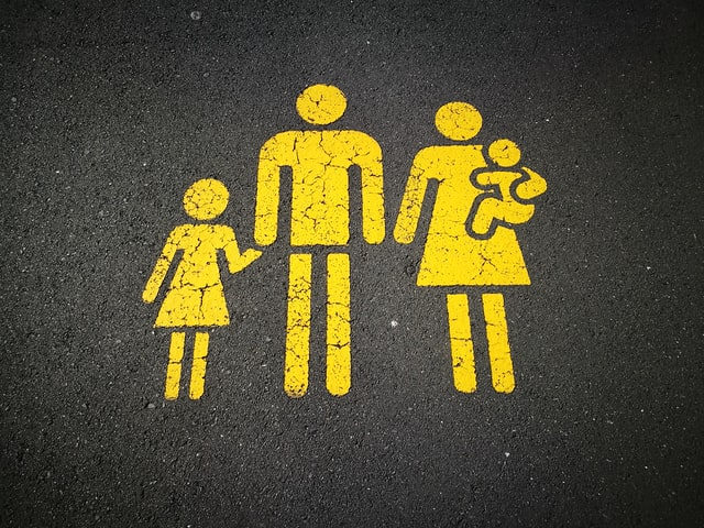 Parking space for families. Yellow outline of family on asphalt.