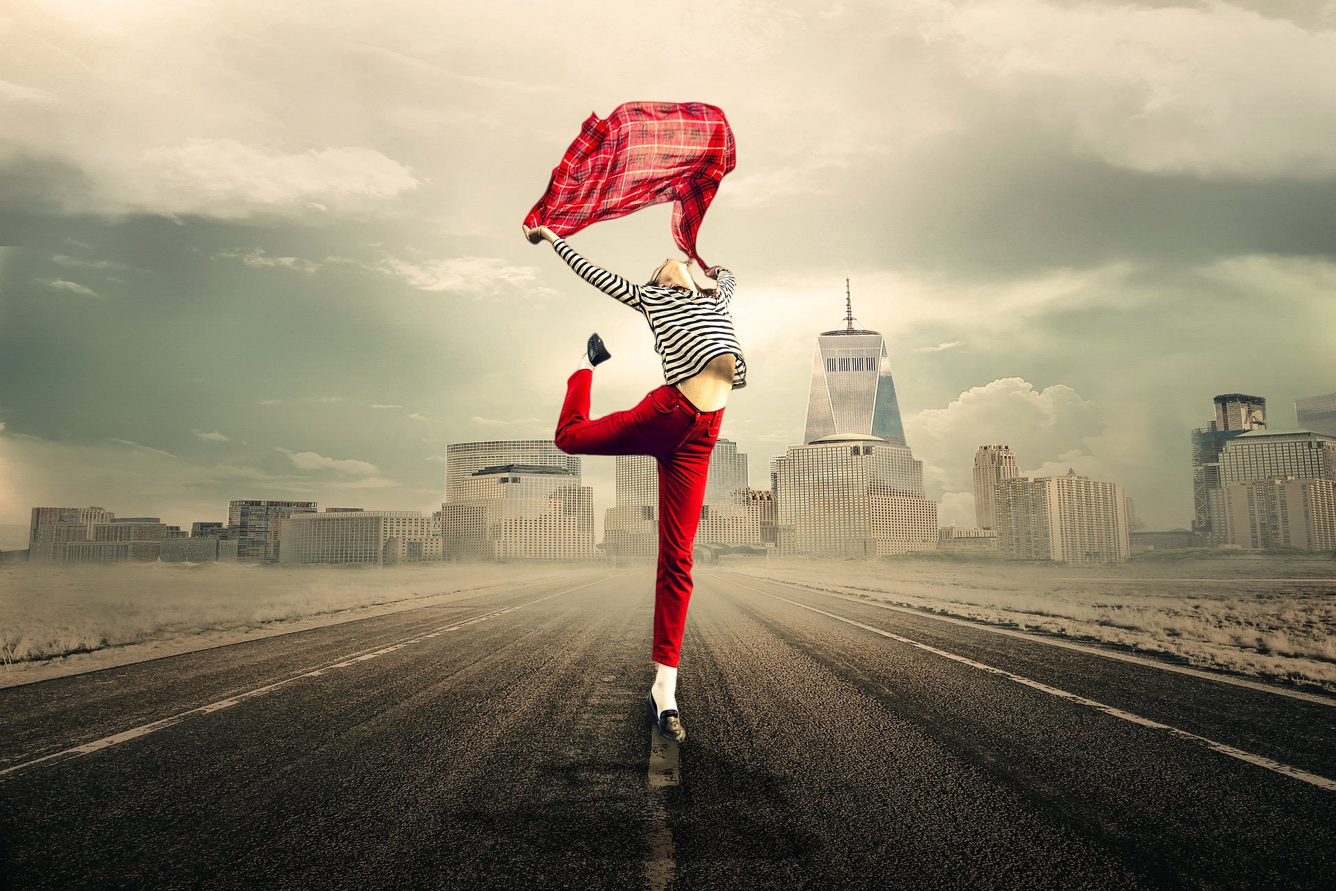 A young woman dancing outside a large city on the highway