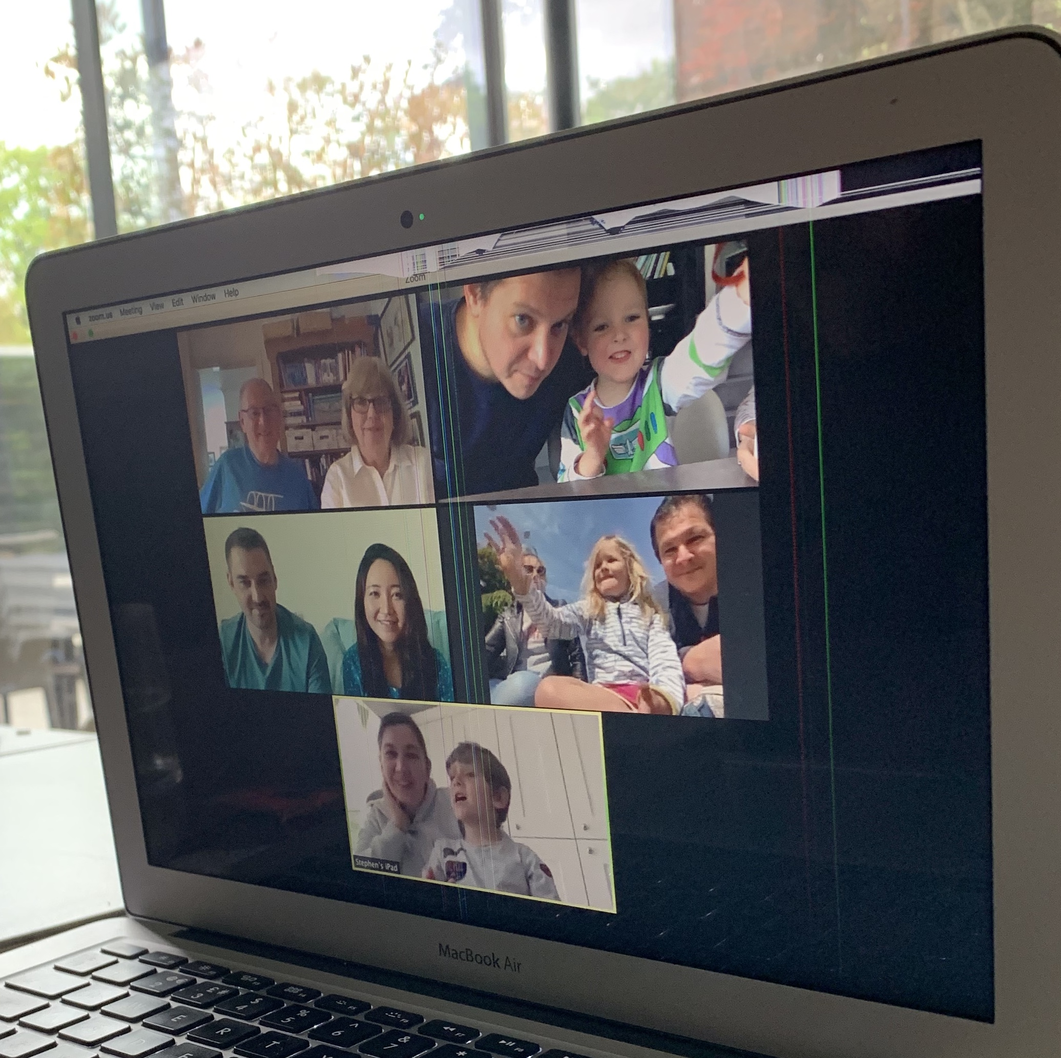 Laptop computer screen showing a family having a zoom call