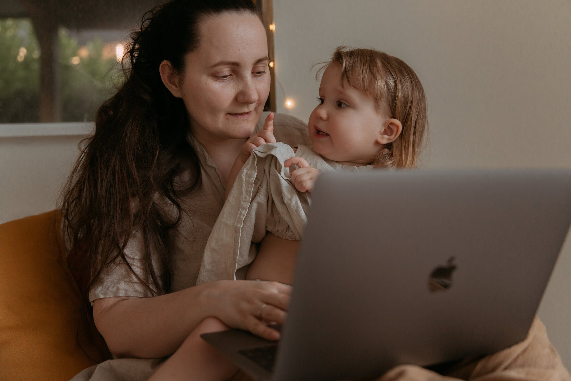 Mom working on her laptop and holding her baby