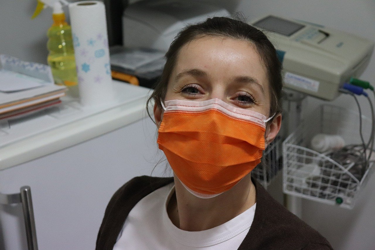 A female healthcare worker wearing a smile under an orange surgical mask