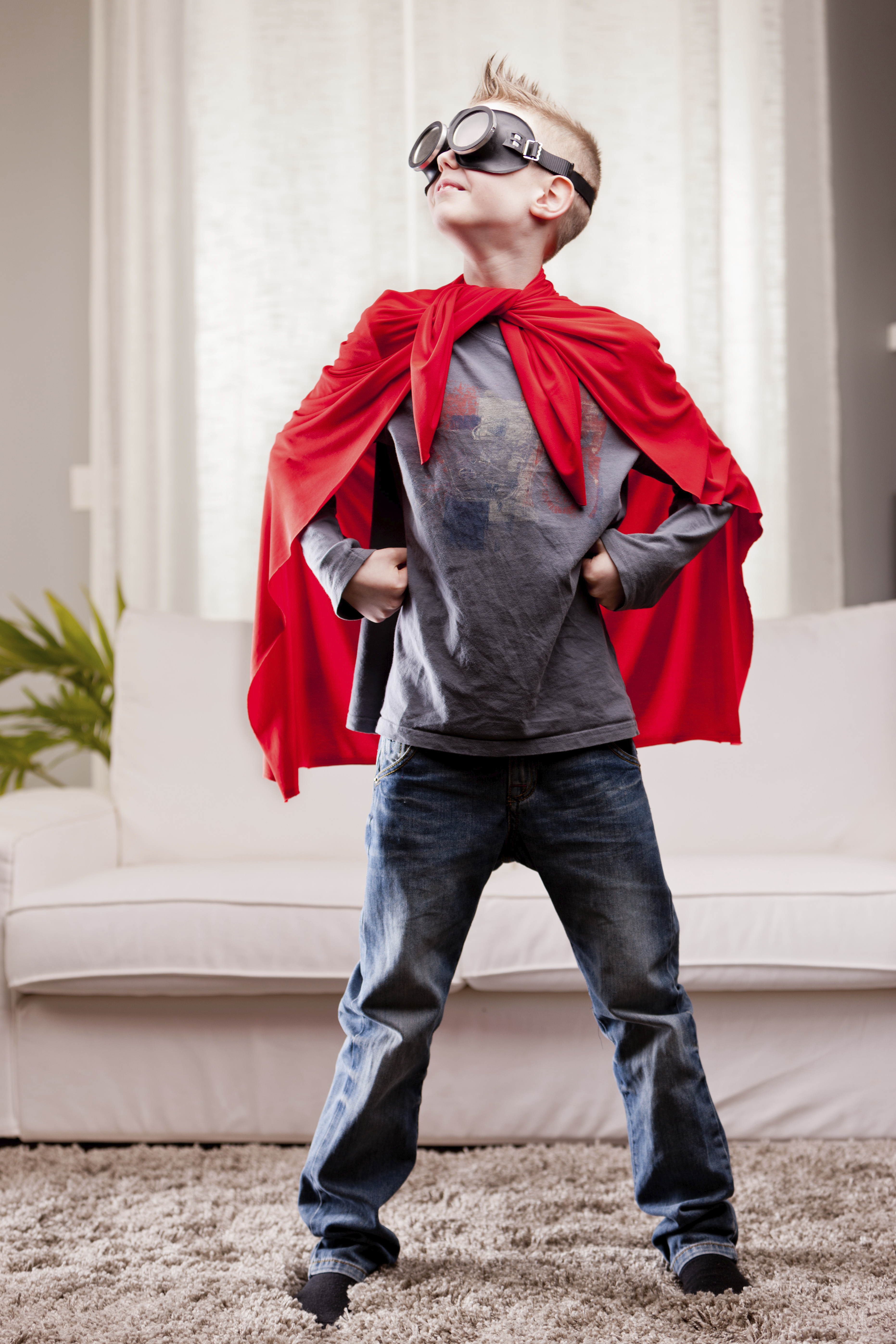 a little kid playing as a red cloak serious superhero