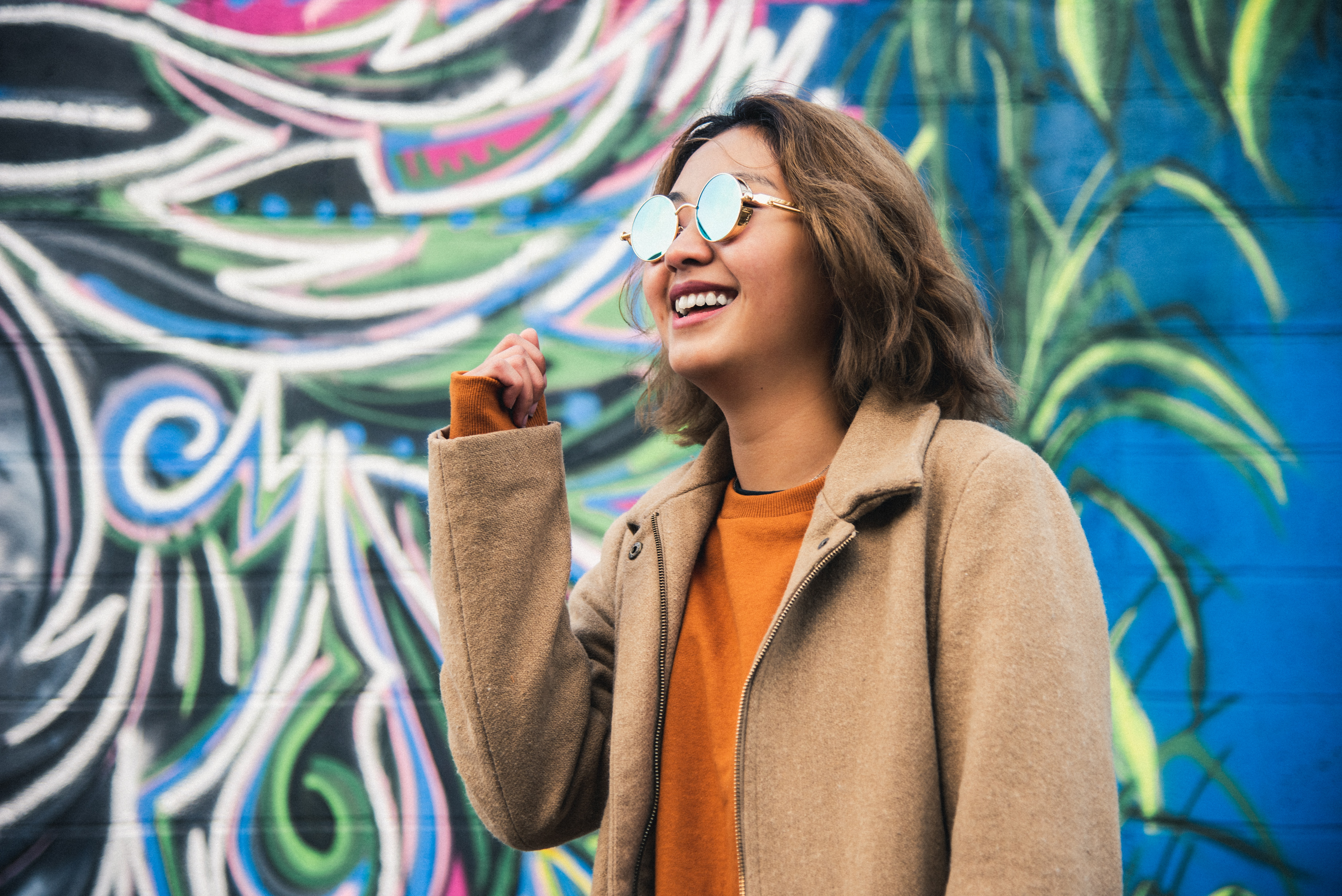A young woman with reflective glasses stands in front of a graffiti wall. She is smiling and wers an orange shirt and tan coat.