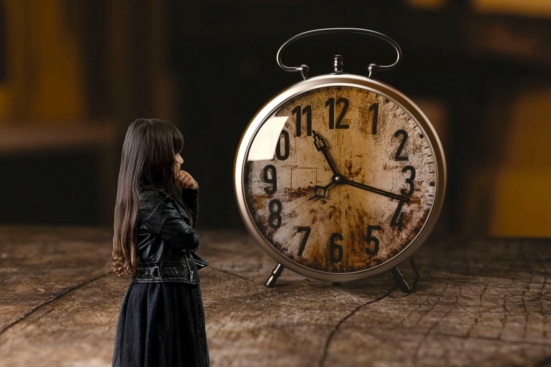 Small girl in black standing in front of a large alarm clock.