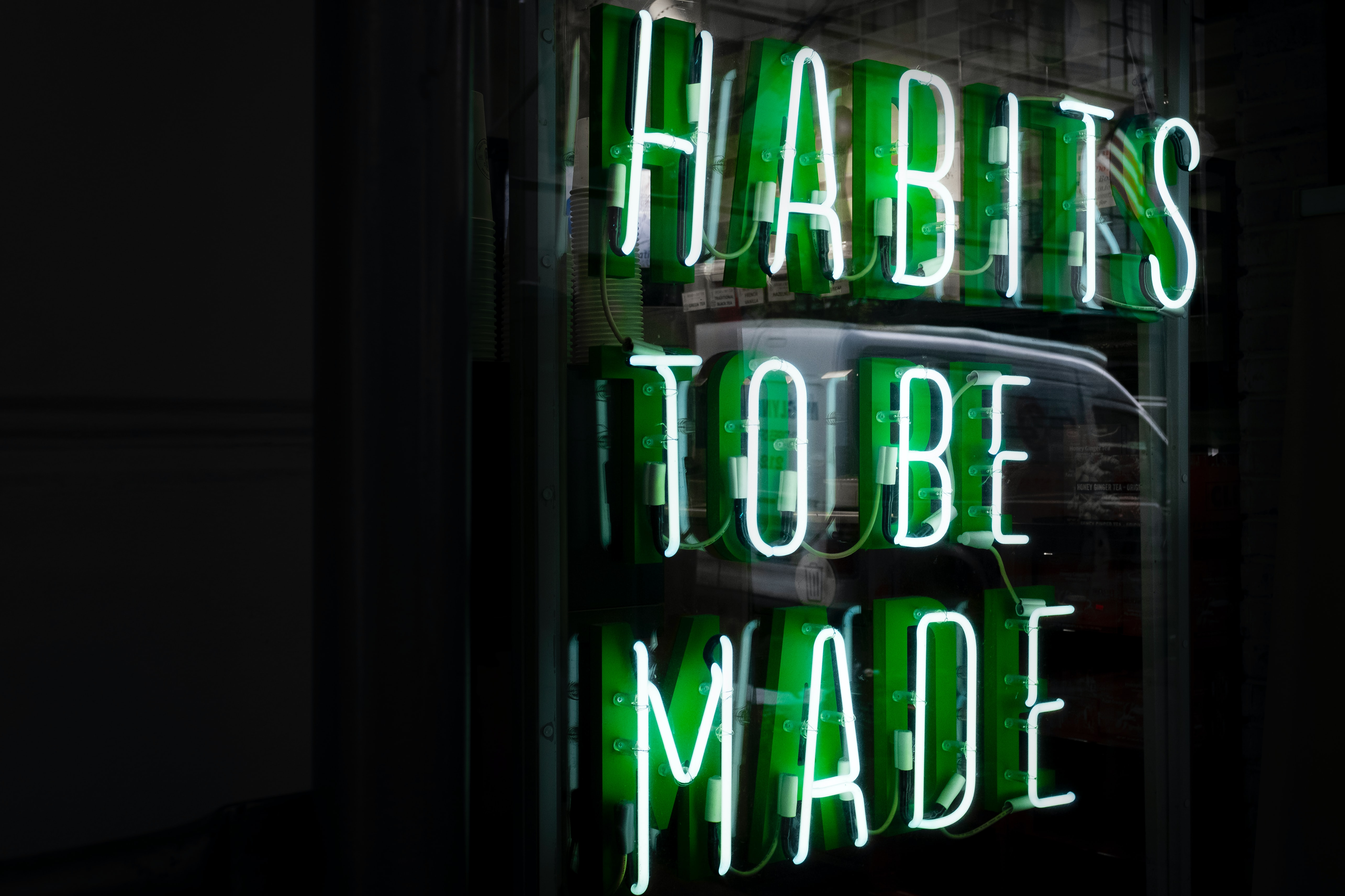 green neon sign reading habits to be made