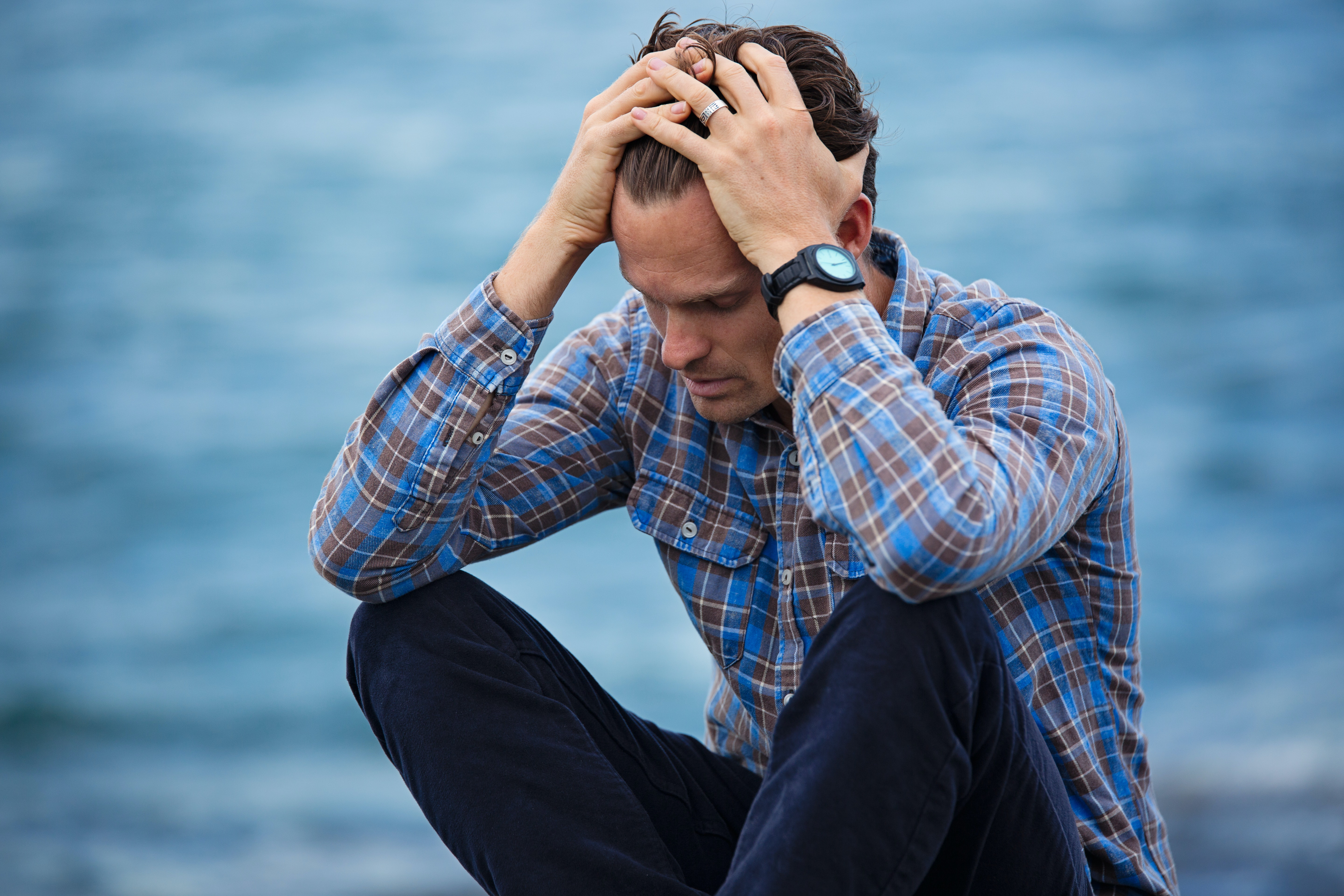 Man in blue and red striped shirt sitting down holding his head and staring at the ground