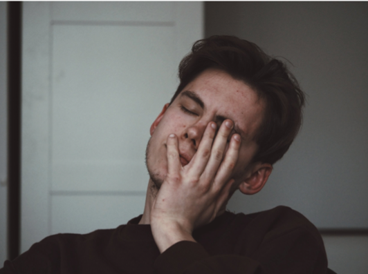 young man looks frustrated and exhausted with his head in his hands