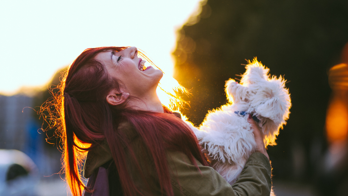 Girl laughing with fluffy white dog outdoor