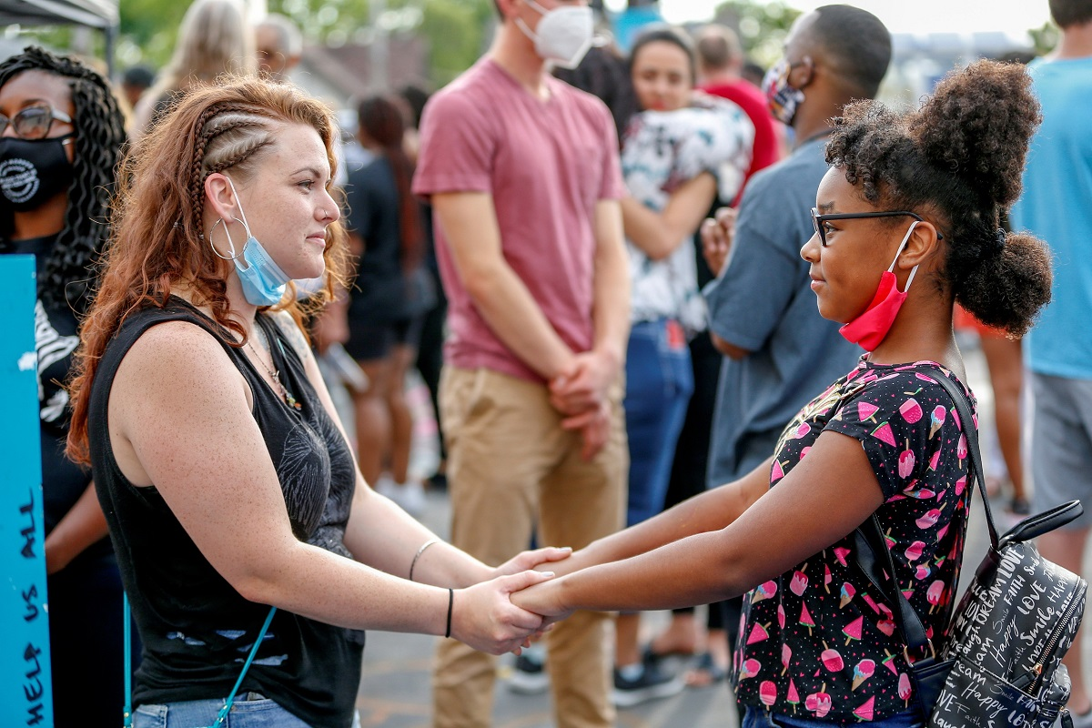 Two women hold hands during a reconciliation revival, part of an event to mark Juneteenth, which commemorates the end of slavery in Texas, two years after the 1863 Emancipation Proclamation freed slaves elsewhere in the United States, amid nationwide protests against racial inequality in Minneapolis, Minnesota, U.S. June 19, 2020. REUTERS/Eric Miller