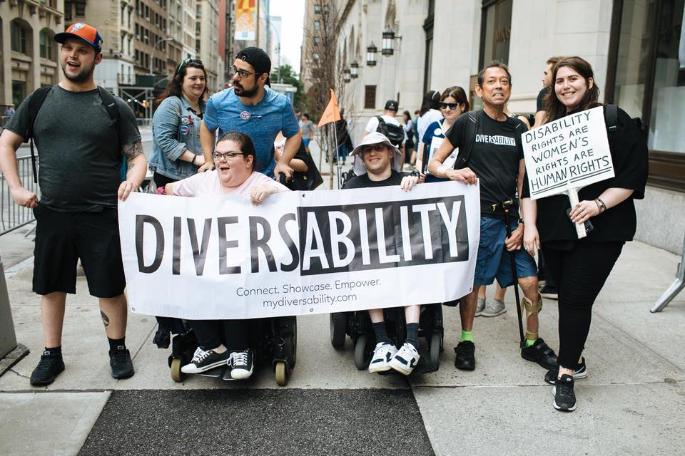 """A photograph of a group of Diversability community members walking in New York City's 2018 Disability Pride Parade. Four people are holding a Diversability banner. Another person is holding a sign that reads """"disability rights are women's rights are human rights."""" This sign is written in all capital letters, and """"human rights"""" is underlined twice."""