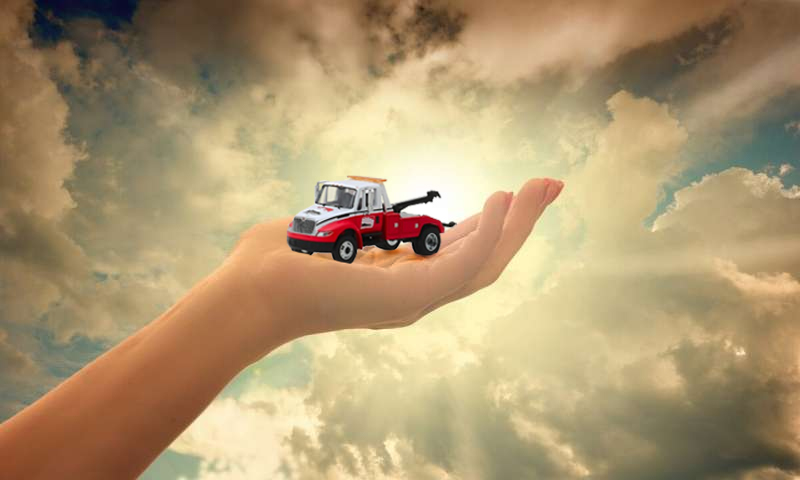 AAA truck held in the hand of God